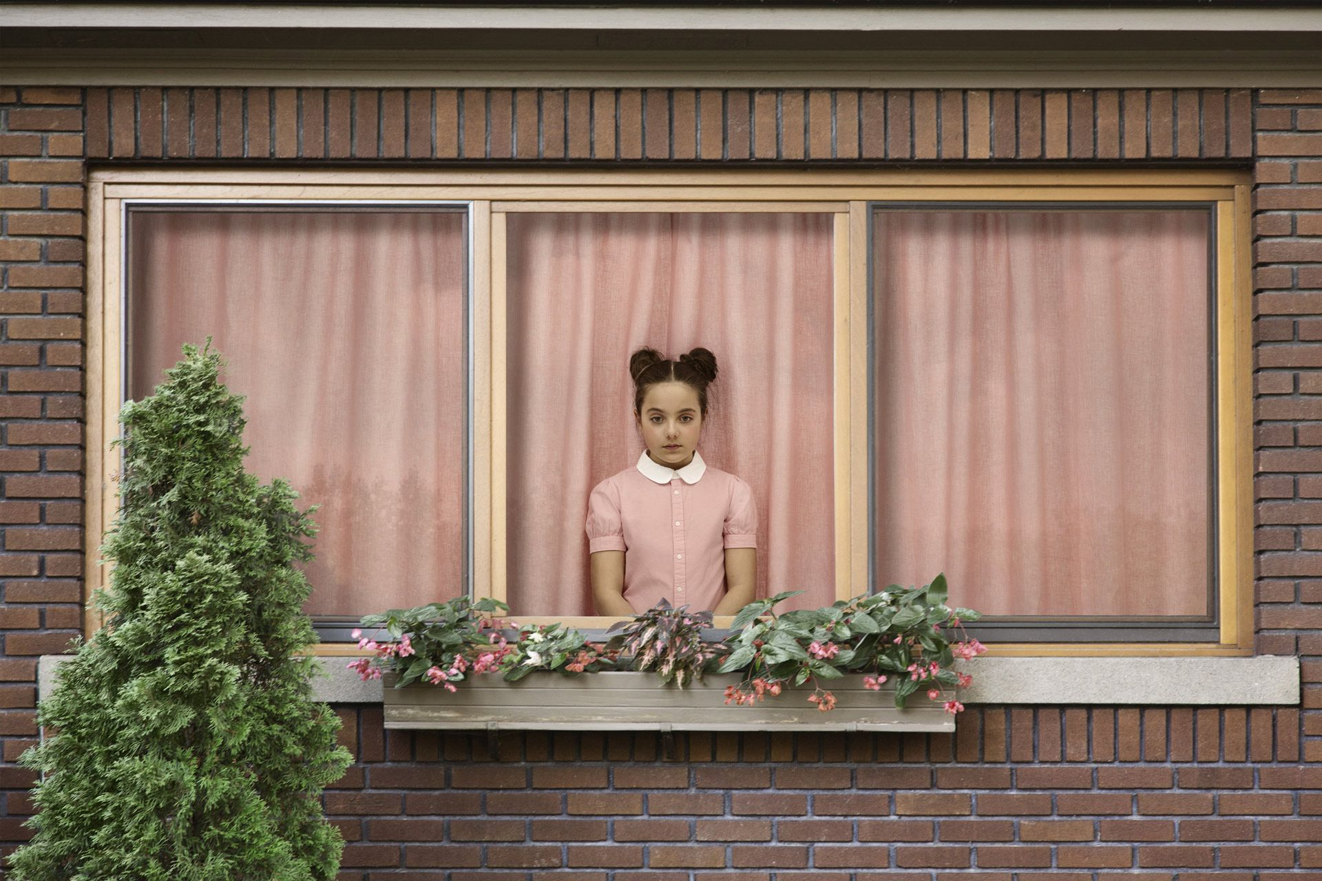 young girl dressed in pink inside house looking sadly out the window by Simon Duhamel for In Between