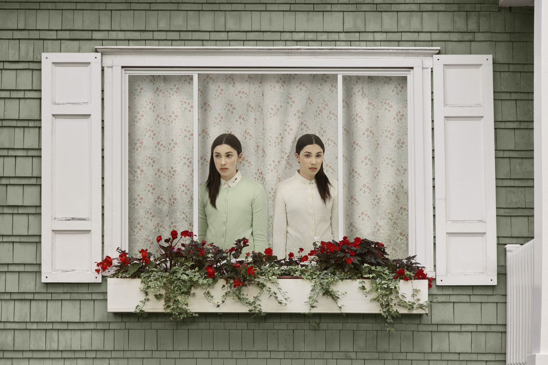 young set of twin girls one in light green one in white inside house looking sadly out the window in different directions by Simon Duhamel for In Between