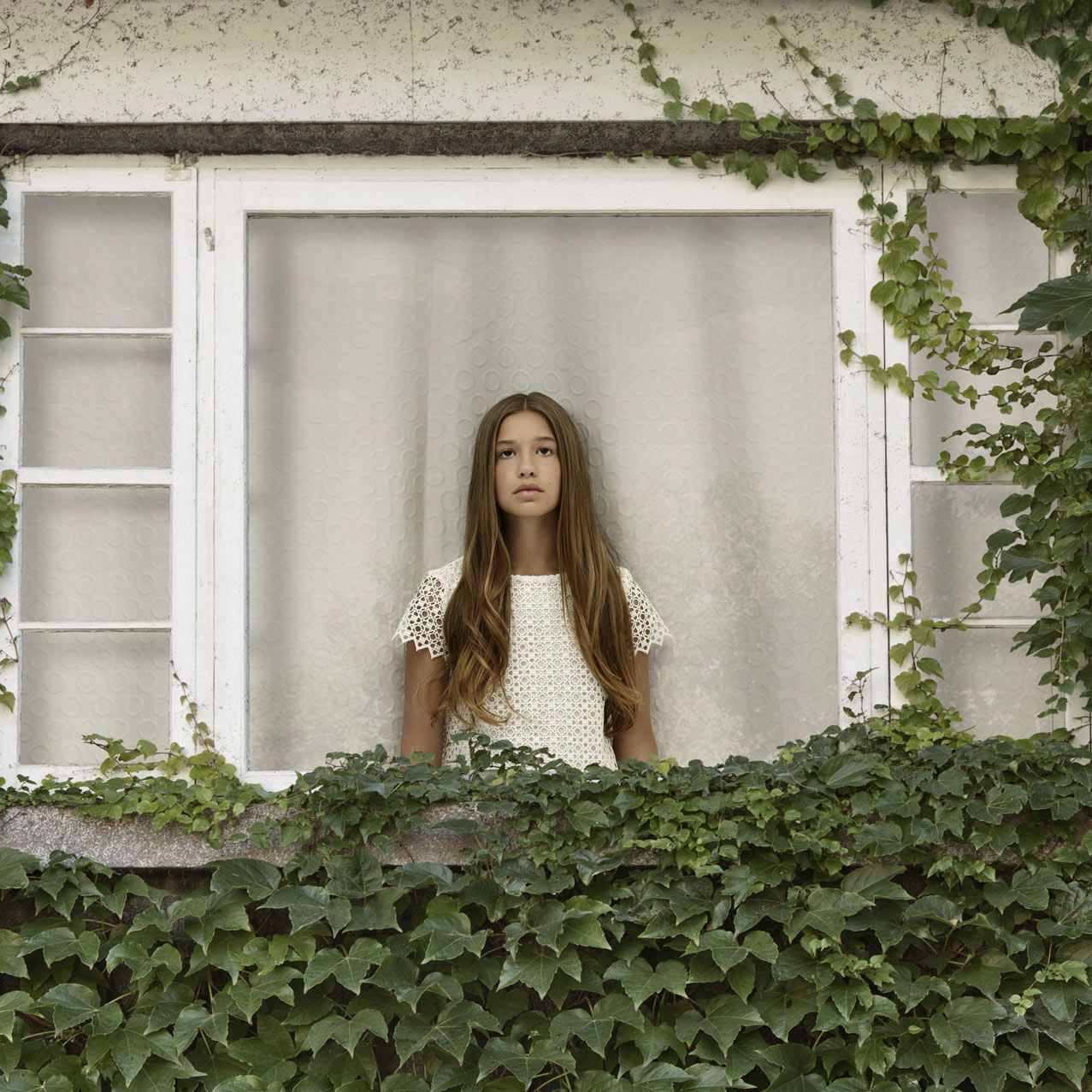 young brown haired girl dressed in white inside vine covered house looking sadly out the window by Simon Duhamel for In Between