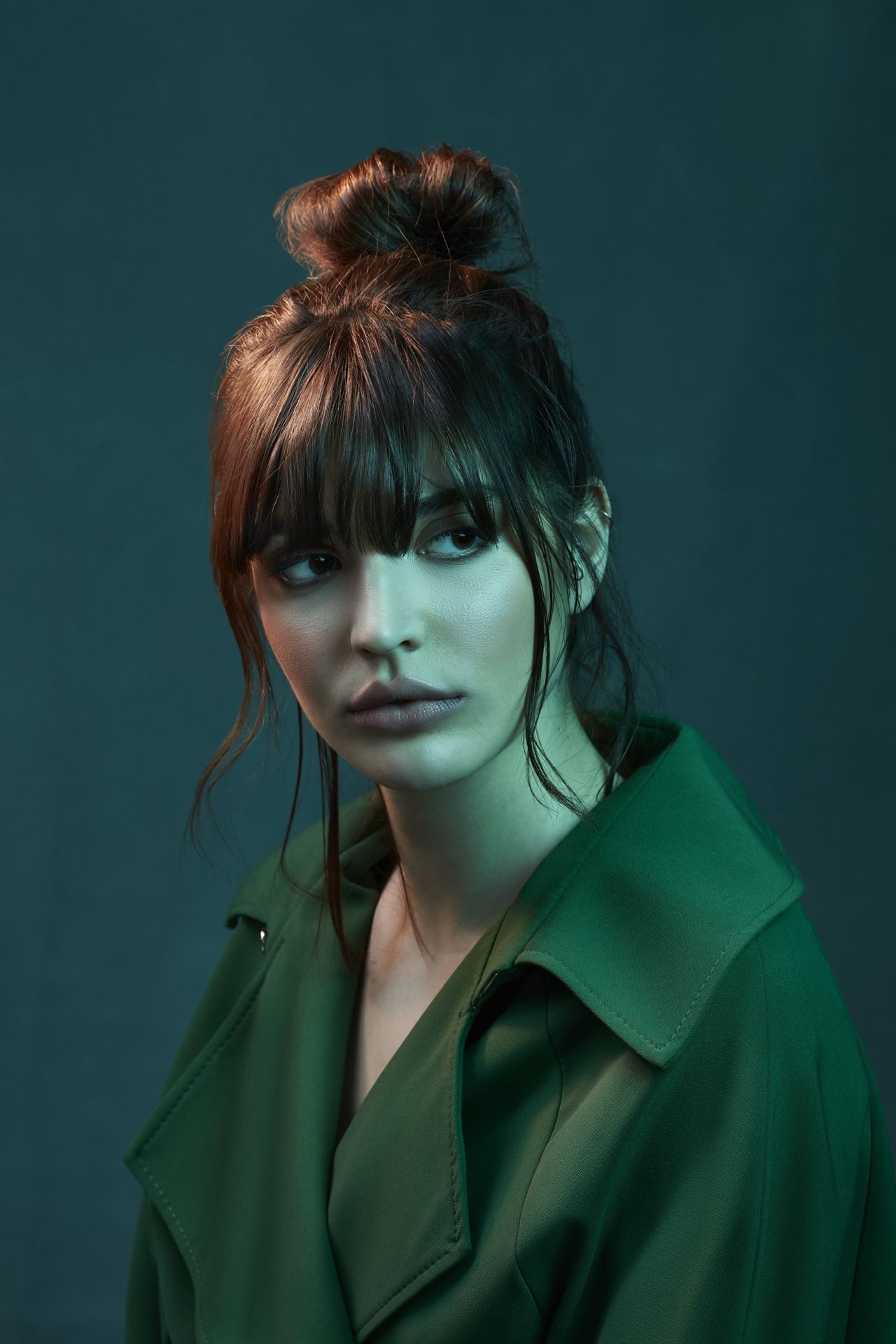 white woman looking pensive hair up wearing dark green blouse on dark green background and colored lighting by Simon Duhamel for creative project Introspect