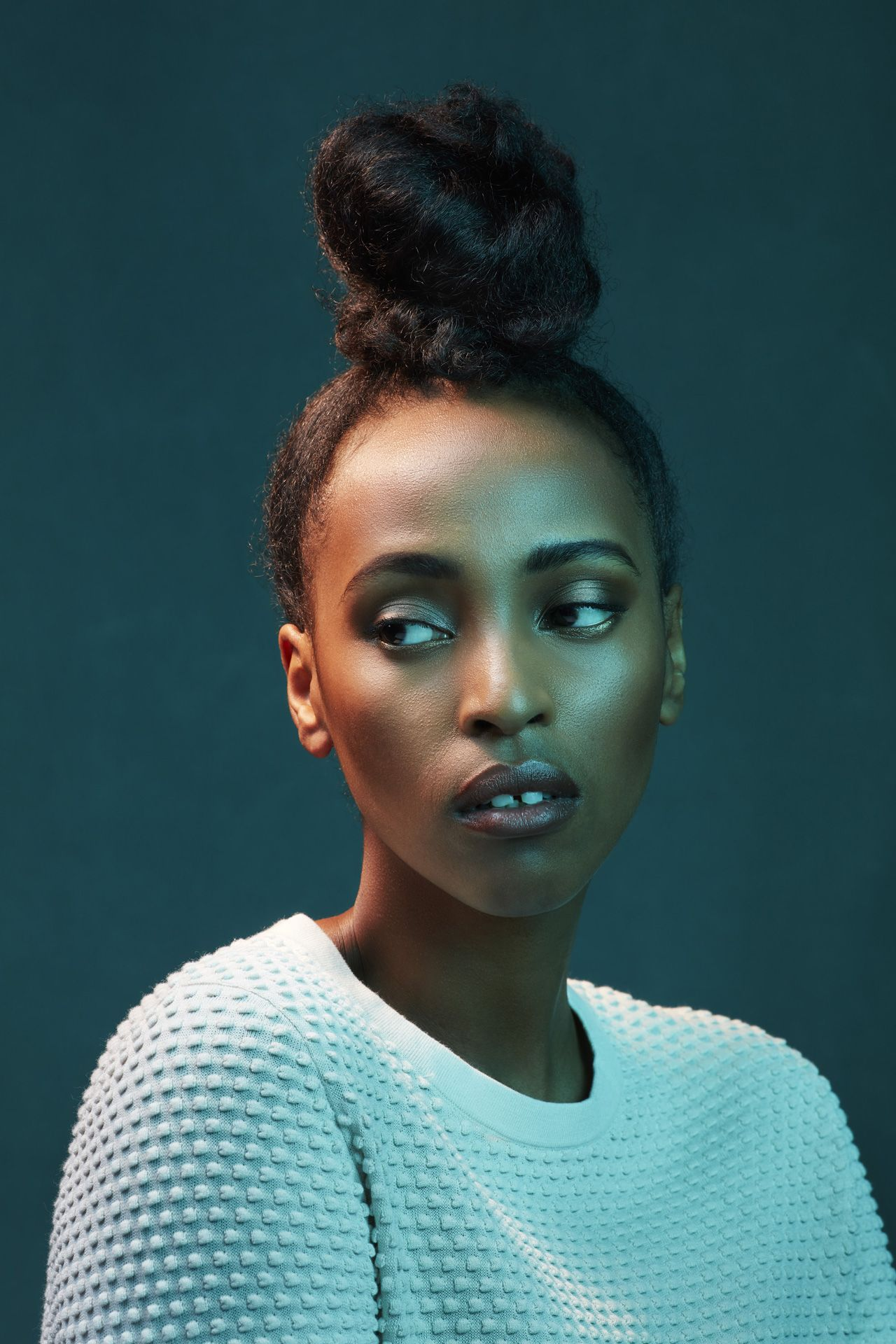 portrait of black woman wearing white textured sweater hair up looking pensively away on dark green background by Simon Duhamel for creative project Introspect