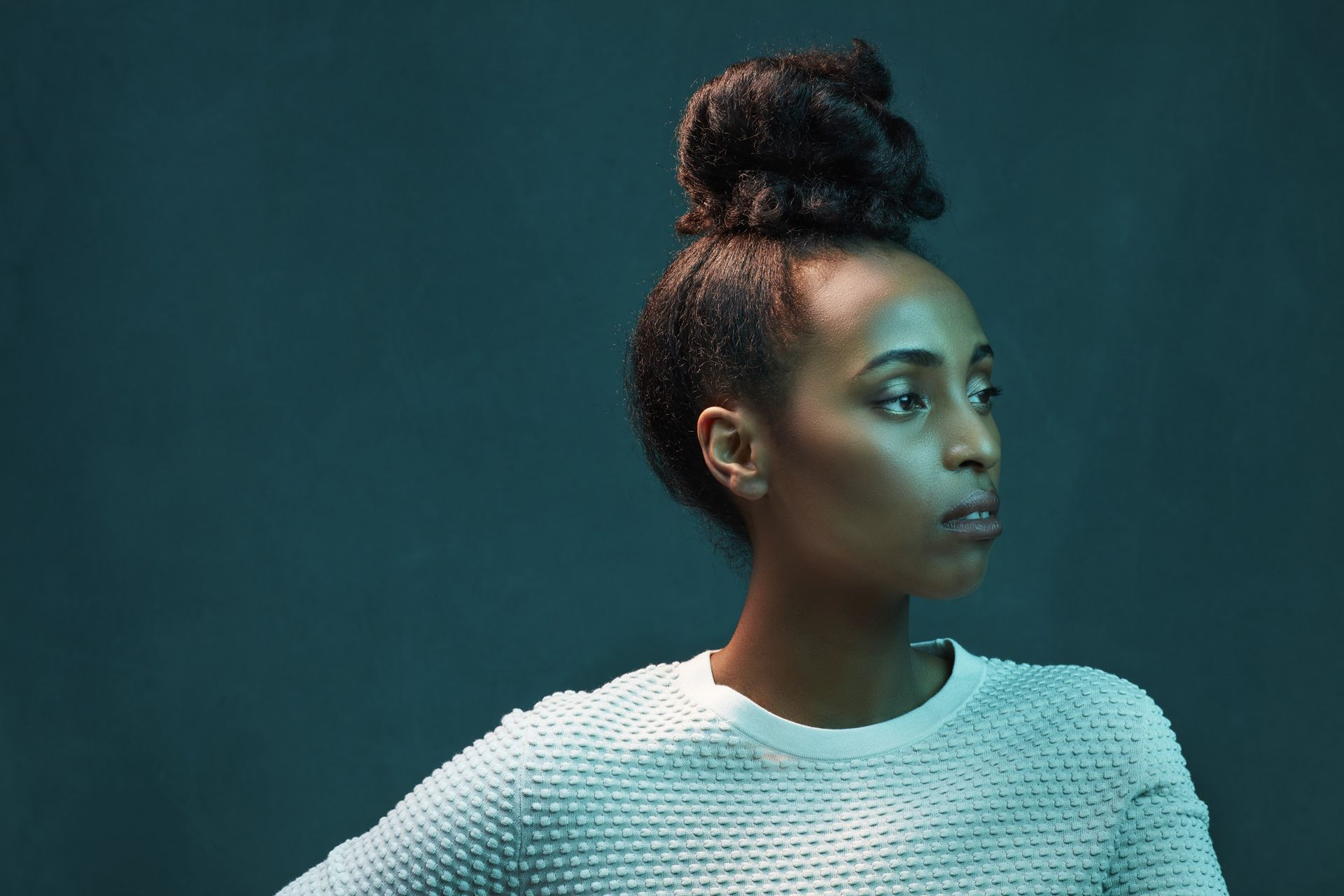 portrait of black woman wearing white blouse hair up looking pensively away on dark green background by Simon Duhamel for creative project Introspect