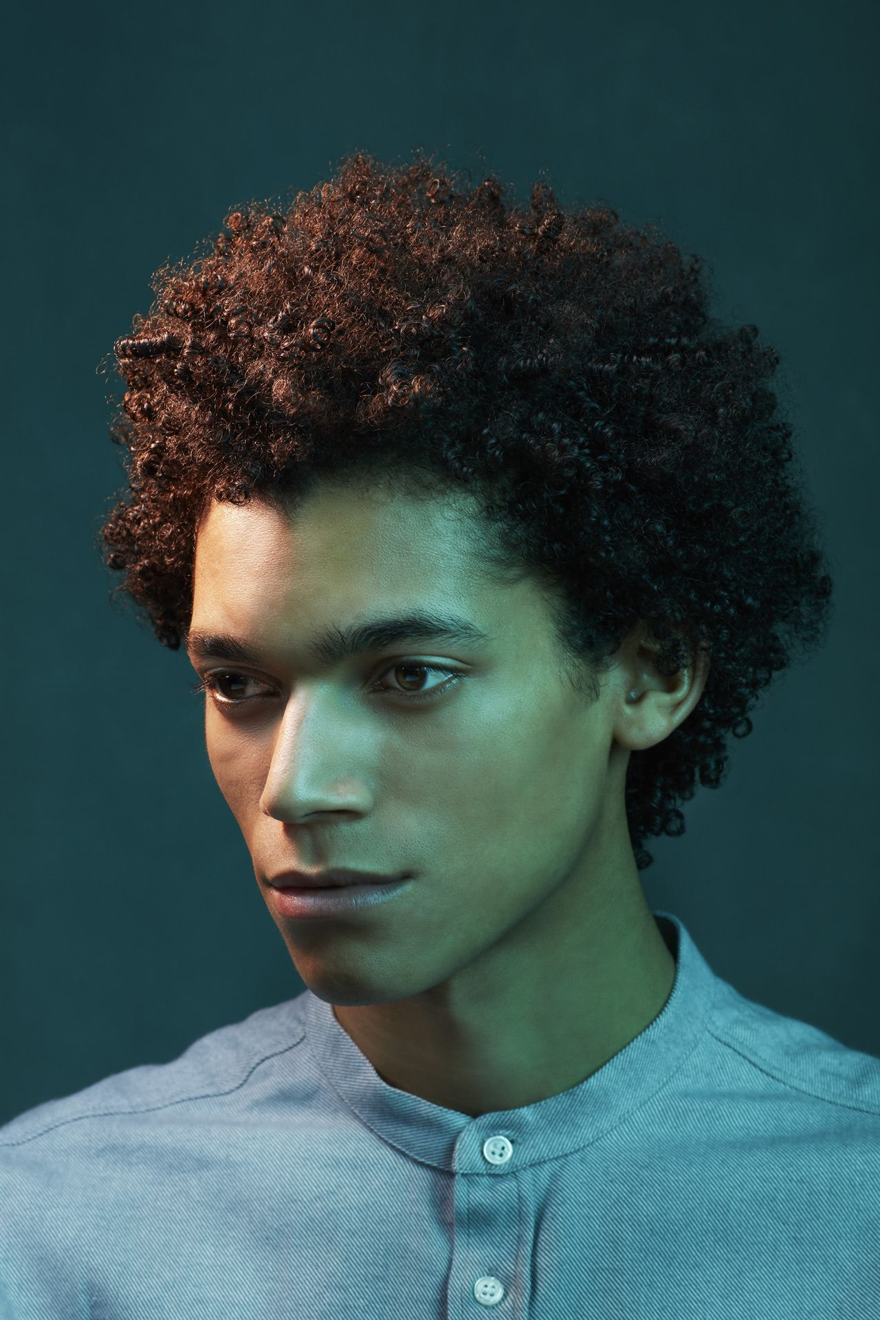 portrait of dark skinned man curly brown hair looking pensive in colored lighting on dark green background by Simon Duhamel for Introspect