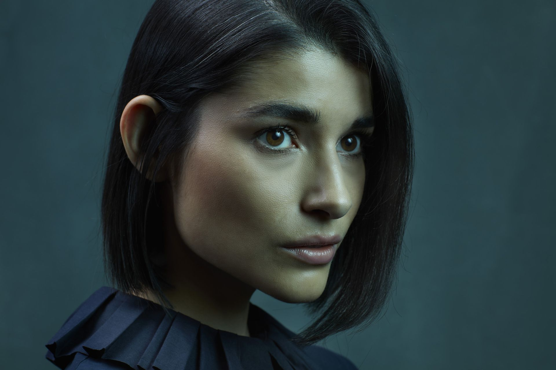 portrait of hispanic woman shoulder length black hair looking pensively away in colored lighting on dark green background by Simon Duhamel for creative project Introspect