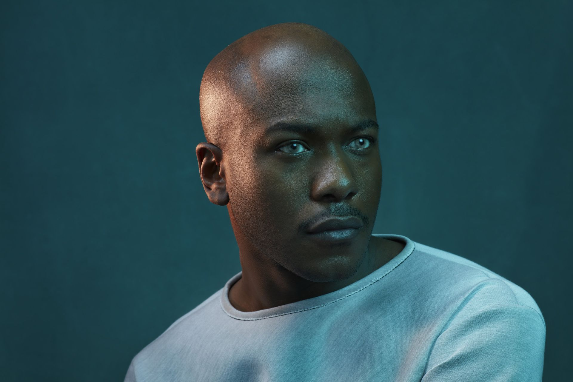 portrait of black man bald wearing white sweater looking pensive in colored lighting on dark green background by Simon Duhamel for creative project Introspect
