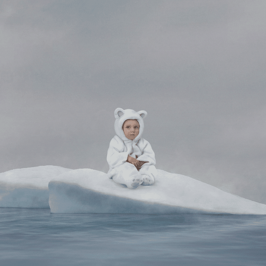 little boy dressed as polar bear crying on melting ice cap in middle of water by Simon Duhamel for Earth Day Lg2