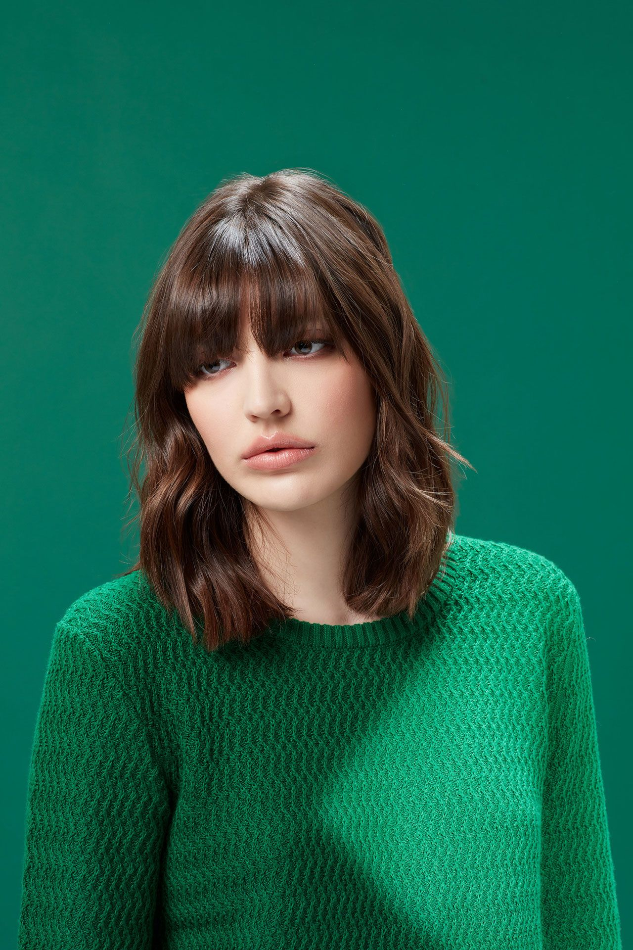 portrait of white woman looking down brown wavy hair down to shoulder wearing textured green sweater on green background by Simon Duhamel for creative project Light & Colours