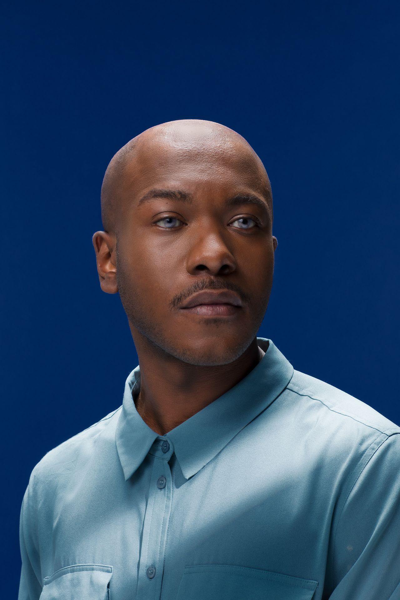 portrait of black man bald light blue eyes wearing light blue buttoned up shirt on dark blue background by Simon Duhamel for creative project Light & Colours