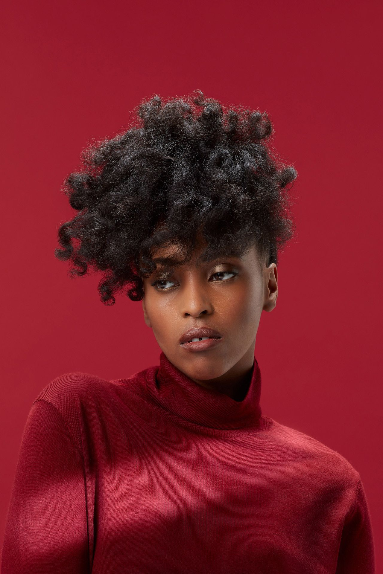 portrait of black woman looking down wearing red turtleneck on red background by Simon Duhamel for creative project Light & Colours