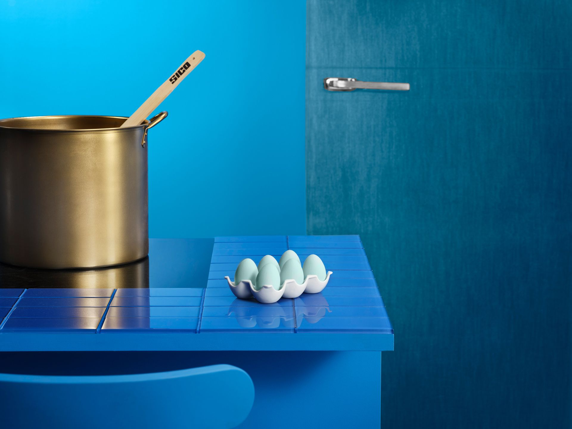 Color blocking of blue : the room is painted blue, the door a different blue, the table a different blue. There is a golden pot and a pack of six light blue eggs.