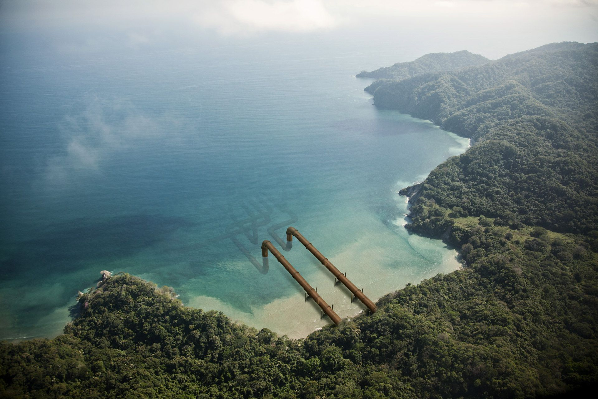 pipelines coming out of an island going into the ocean by Simon Duhamel for Pipeline