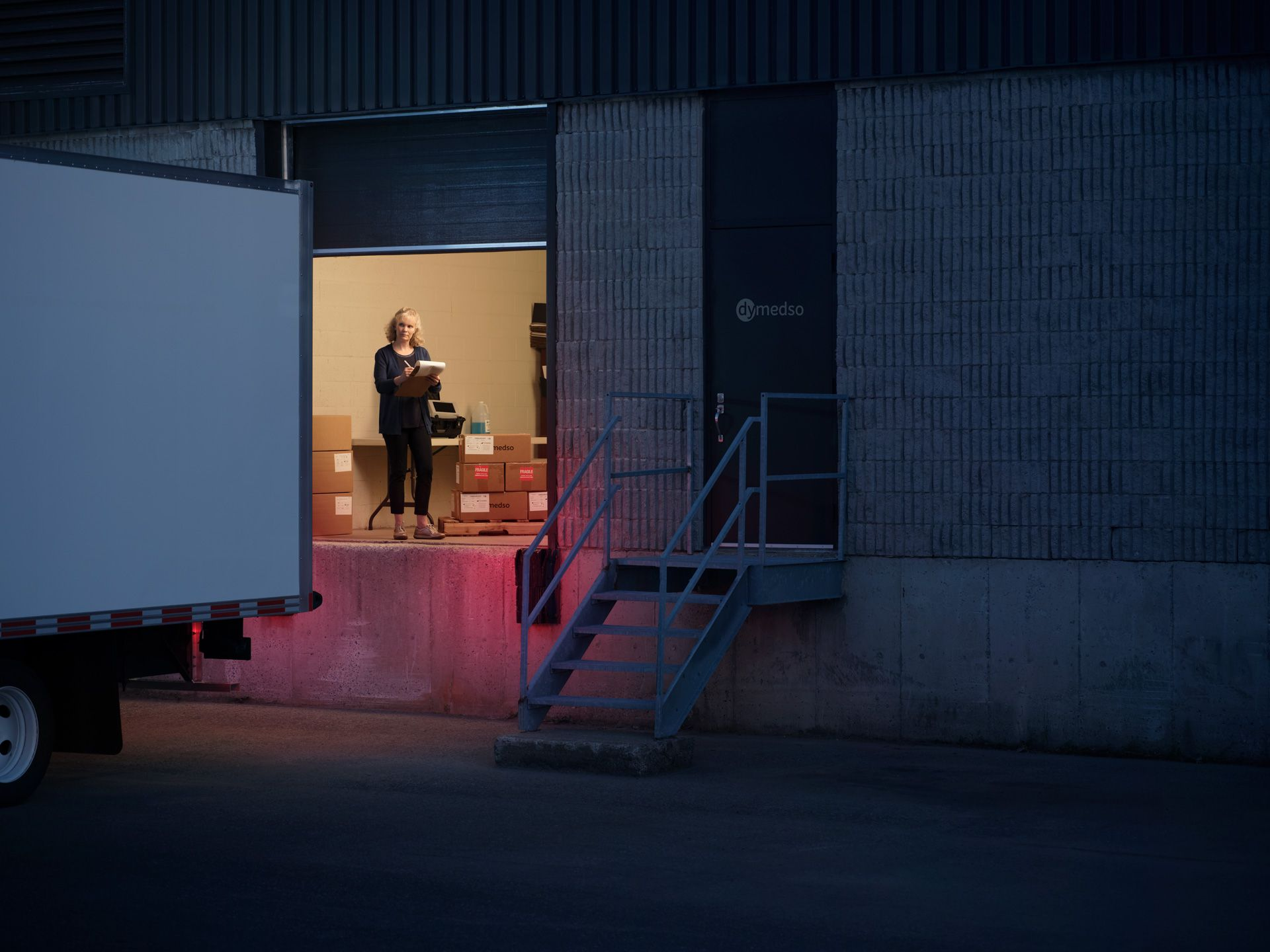 view inside Dymedso loading dock at night with one person working inside photographed by Simon Duhamel for PME MTL in collaboration with K72