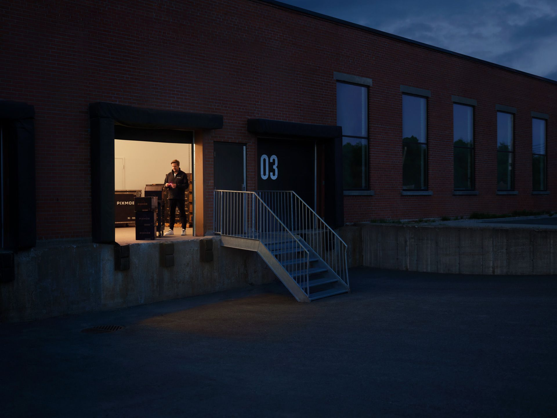 view inside Pixmob loading dock at night with one person working inside photographed by Simon Duhamel for PME MTL in collaboration with K72
