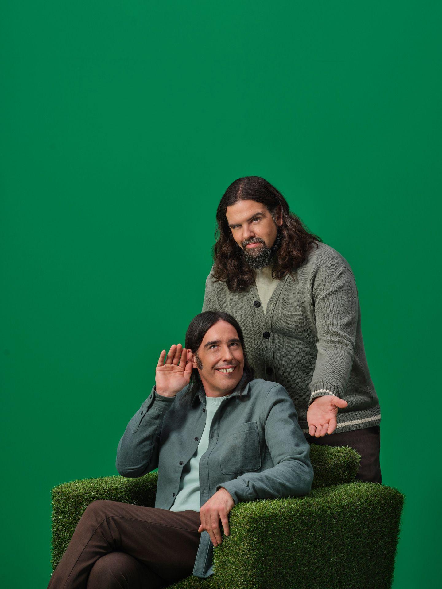 Duo Denis Drolet faisant des grimaces sur un canapé recouvert de fausse herbe et d'un mur vert.