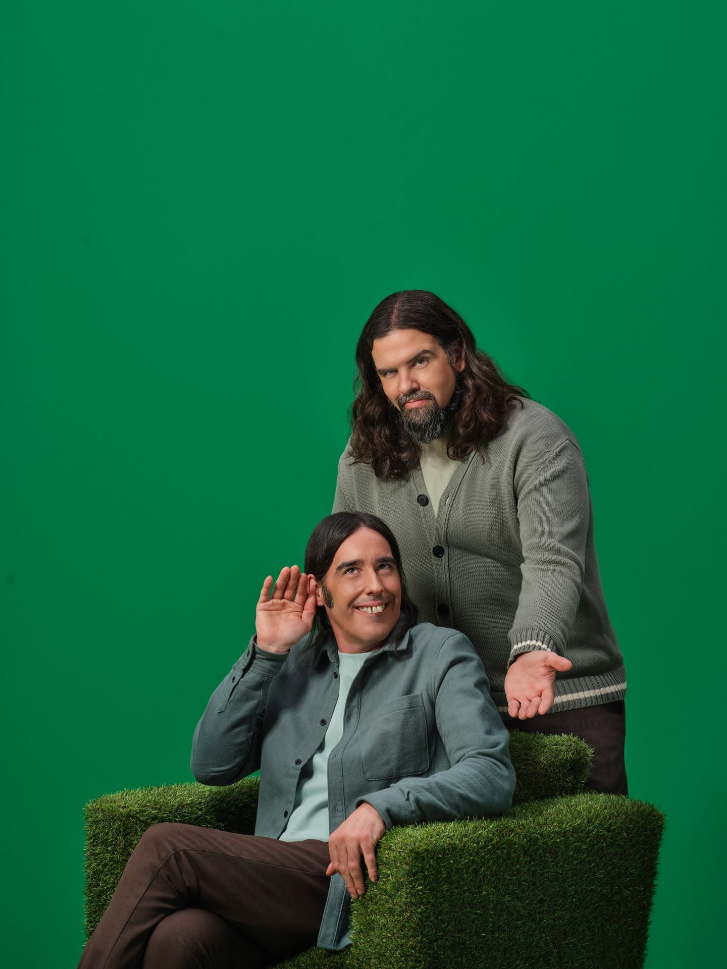 Duo Denis Drolet making funny faces on a sofa covered with fake grass and a green wall.