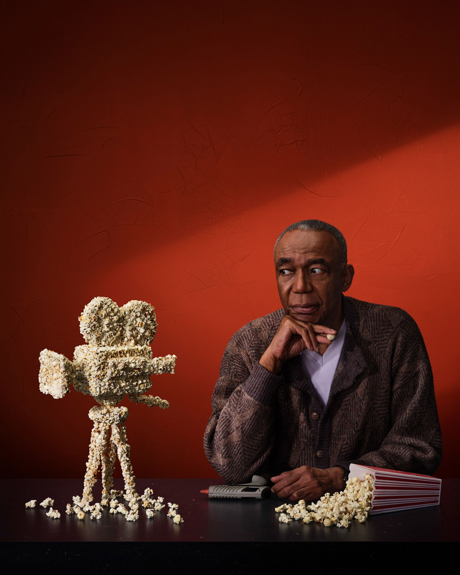 Actor who sculpted a camera with pop corn is staring at his sculpture with his glue gun in front of a red background.