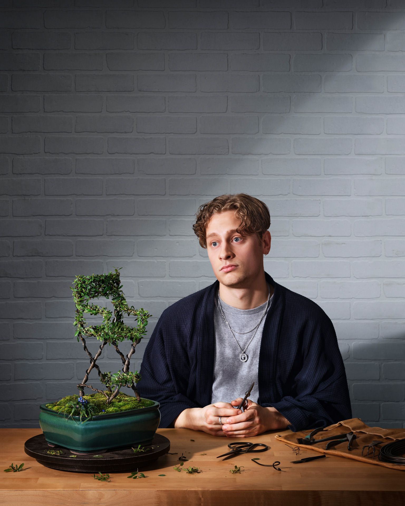 An actor is staring, very blasé, at a bonsai he trimmed in the shape of a movie set chair.