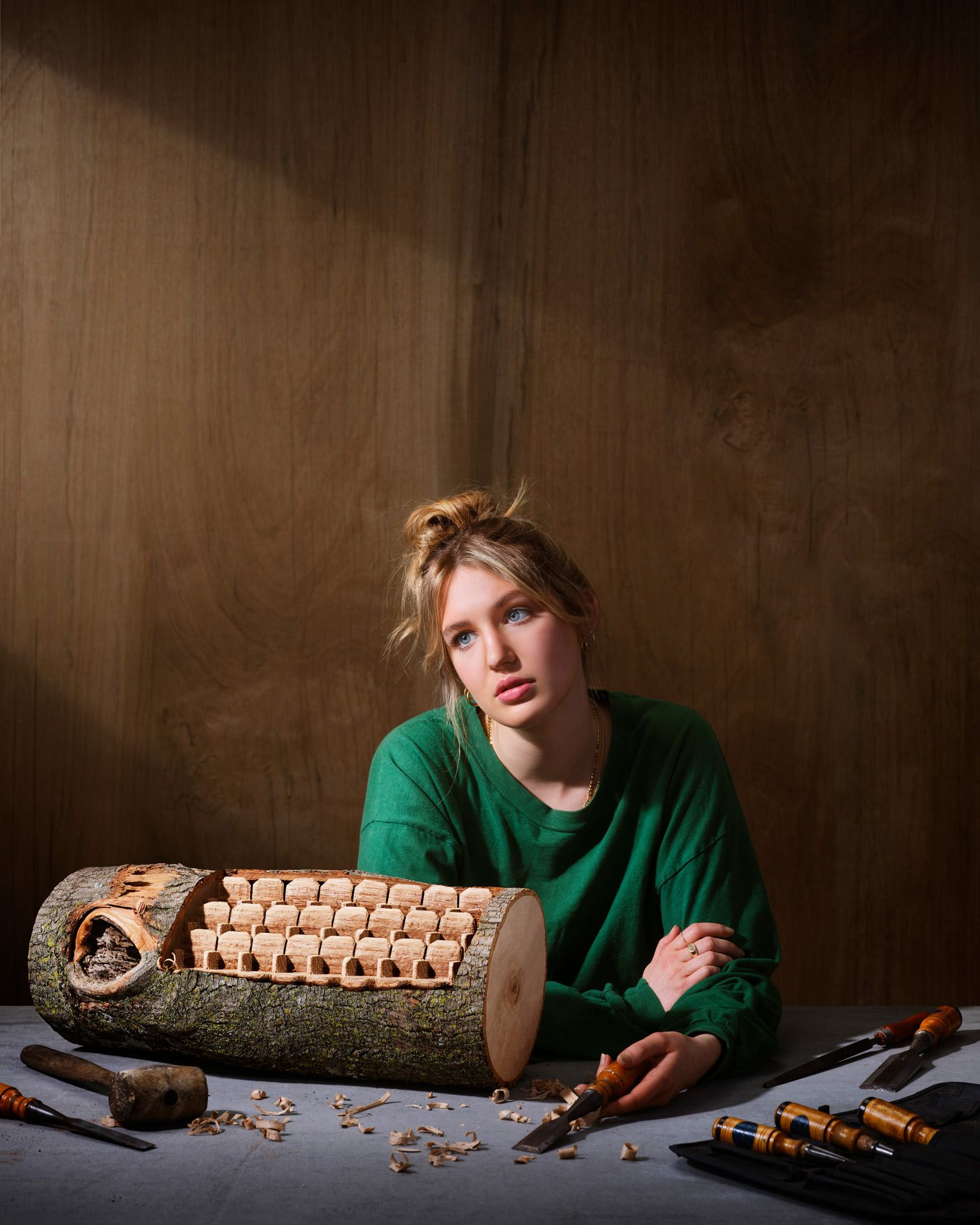 An actress, Sophie Nélisse, is staring at the void with a log of wood she carved into theater movie seating rows.
