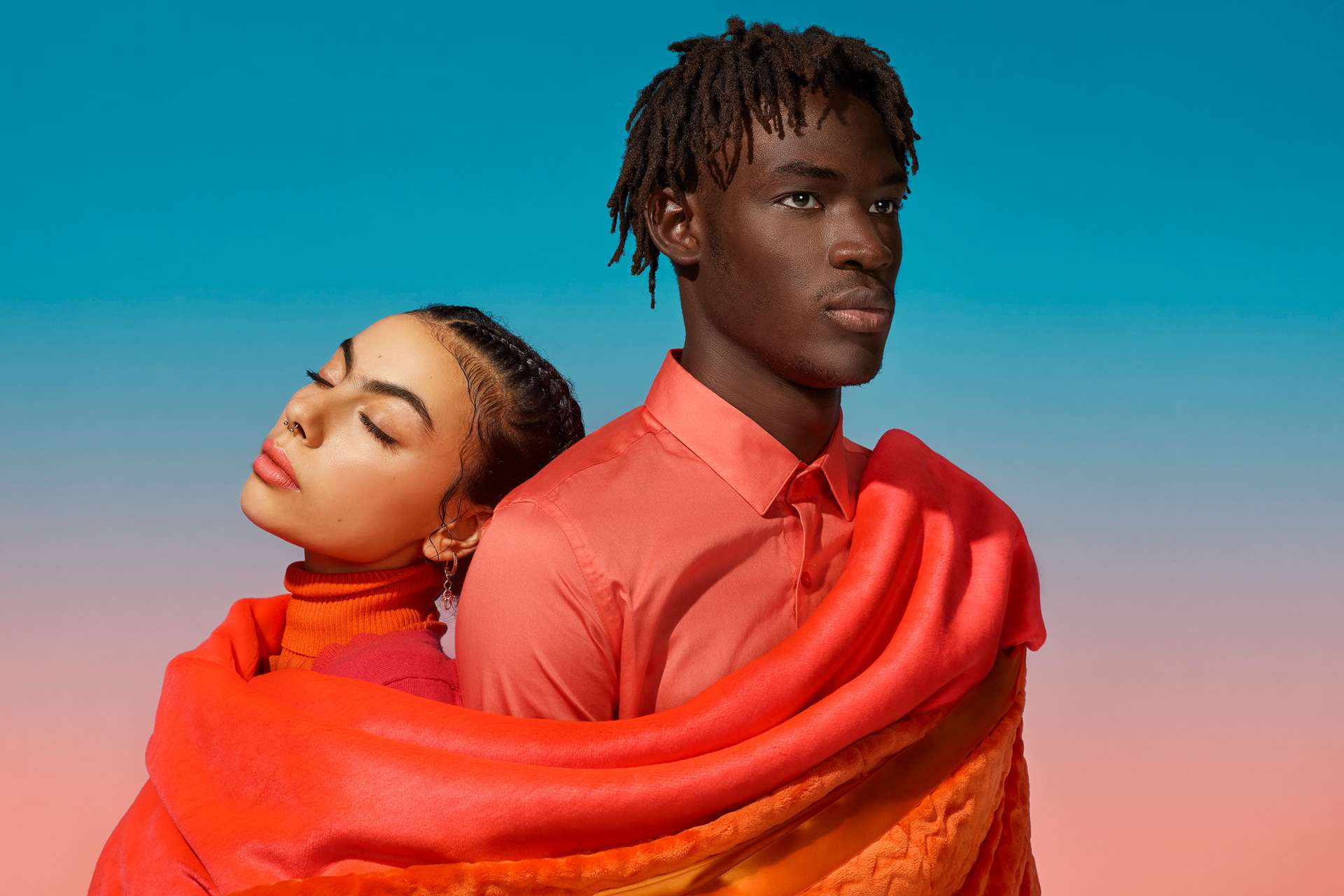 man and woman leaning against each other dressed in layered pieces of fabric by Simon Duhamel for creative project SAND