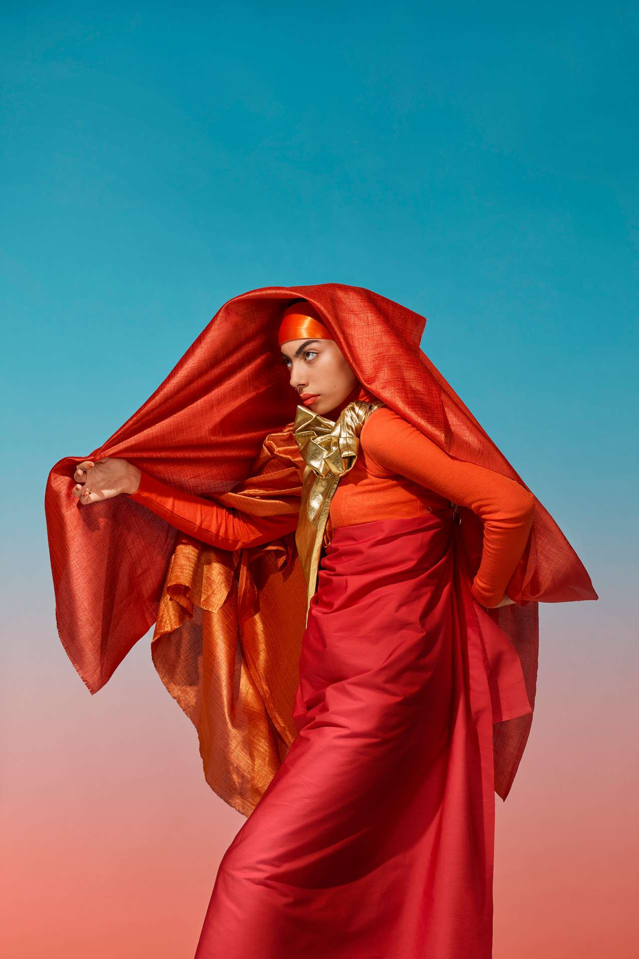 woman of indian origin in layered pieces of red and yellow fabric giving a sari feel emulating indian choreography by Simon Duhamel for SAND