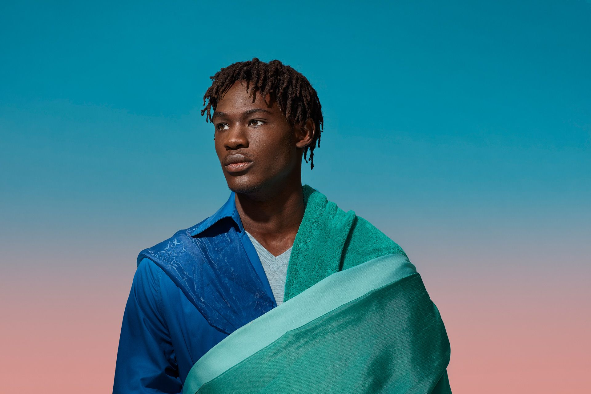 black young man looking ahead dressed in layered pieces of fabric giving a sari feel by Simon Duhamel for SAND