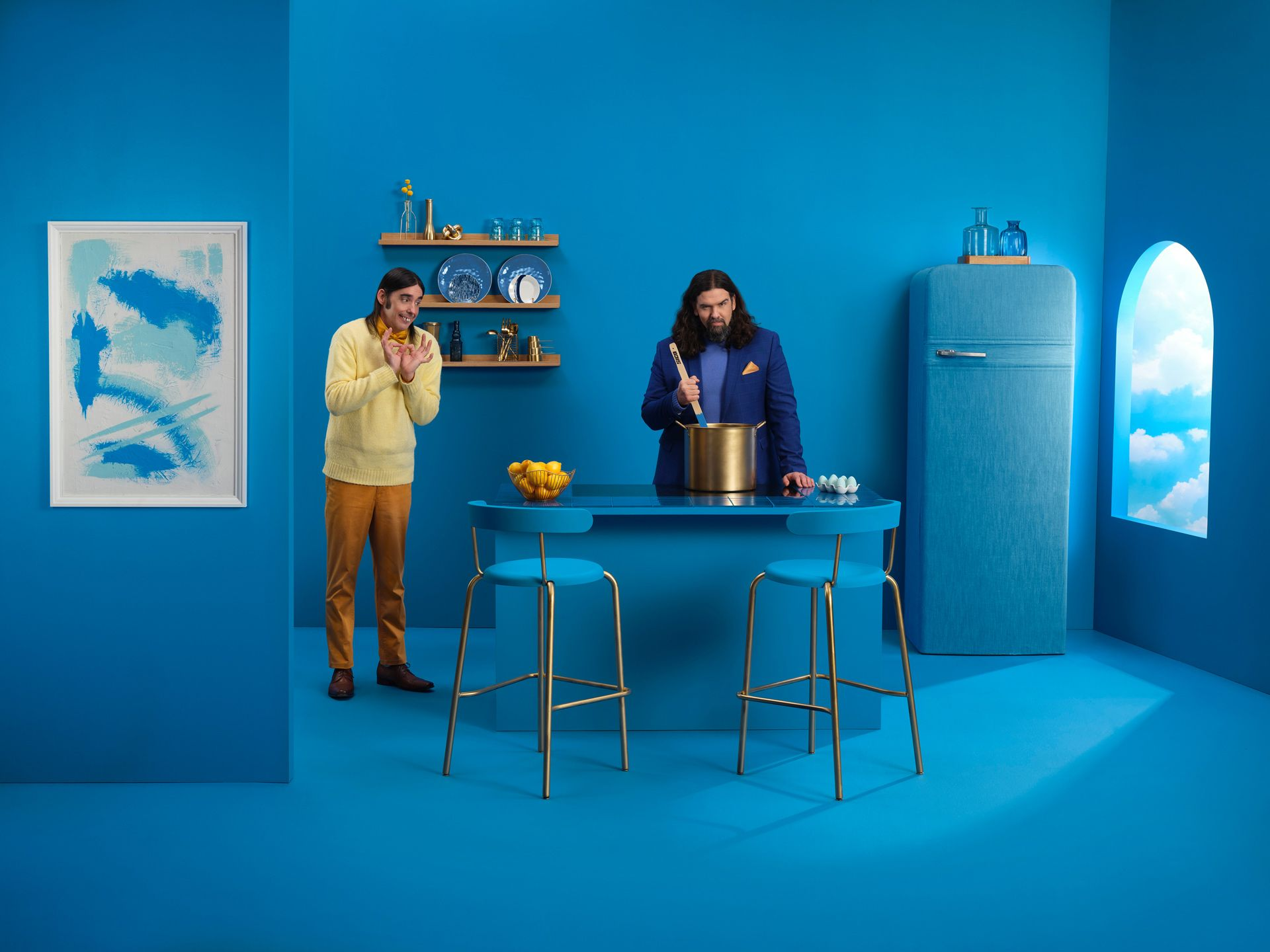 Denis Drolet duo in a kitchen where everything is blue with some gold details. One man is seems to be cooking but he is holding a paint stick.