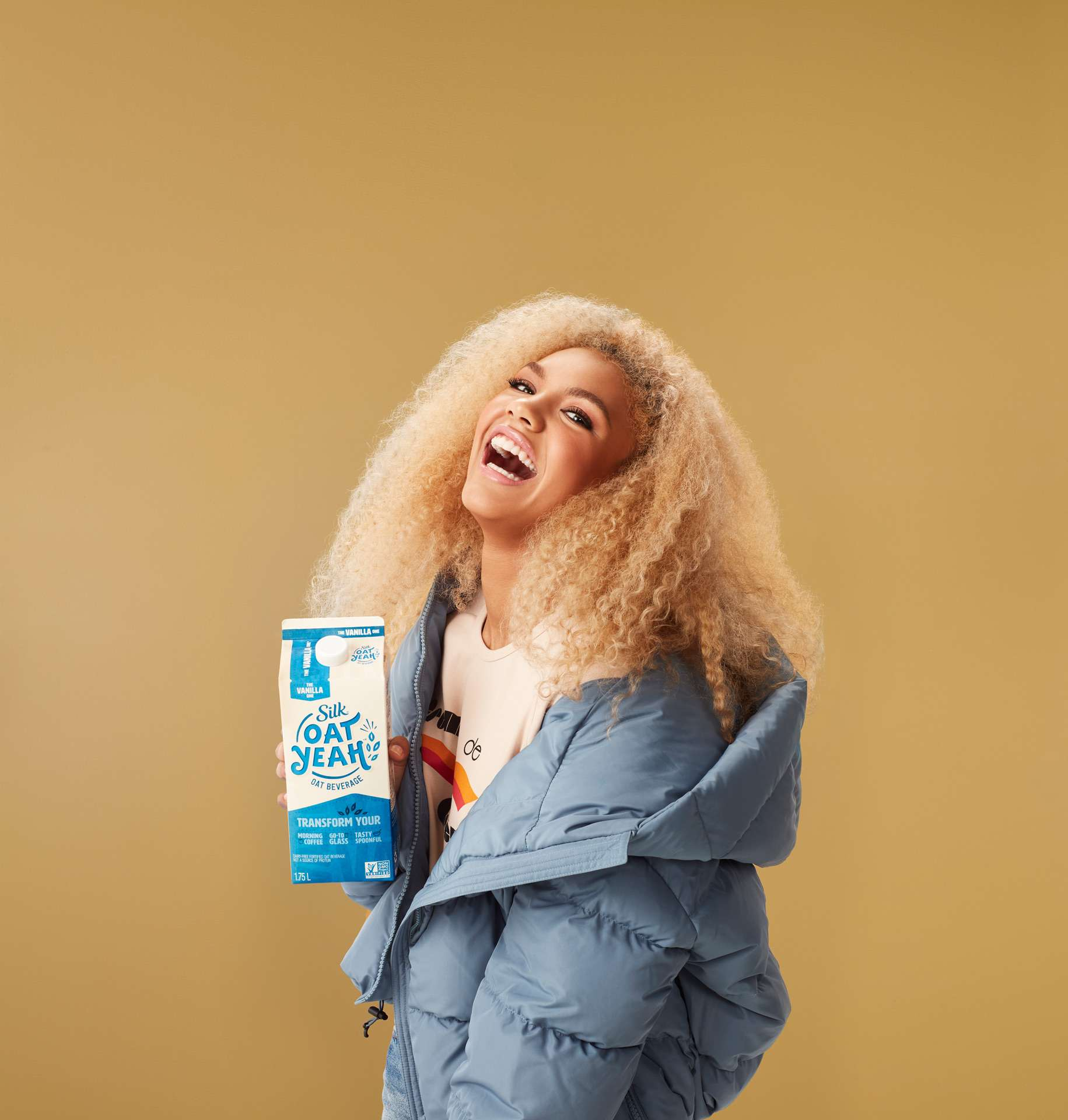 blonde woman big hair laughing wearing baby blue parka holding carton of vanilla oat milk by Simon Duhamel for Oat Yeah Silk and Carl agency
