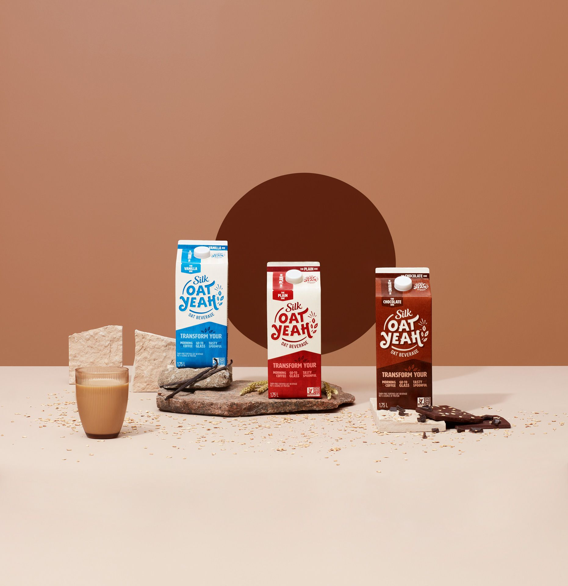 three carton of plain vanilla and chocolate oat milk with ingredients around and glass full beside by Simon Duhamel for Oat Yeah Silk and Carl agency
