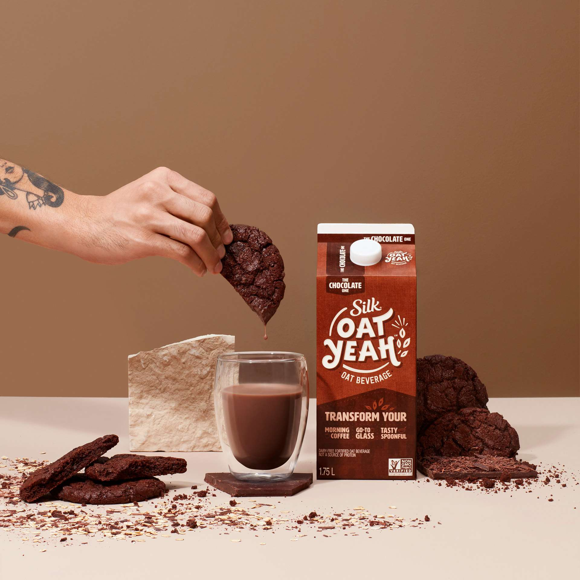 carton of chocolate oat milk glass full in front hand dunking a chocolate cookie in glass by Simon Duhamel for Oat Yeah Silk and Carl agency