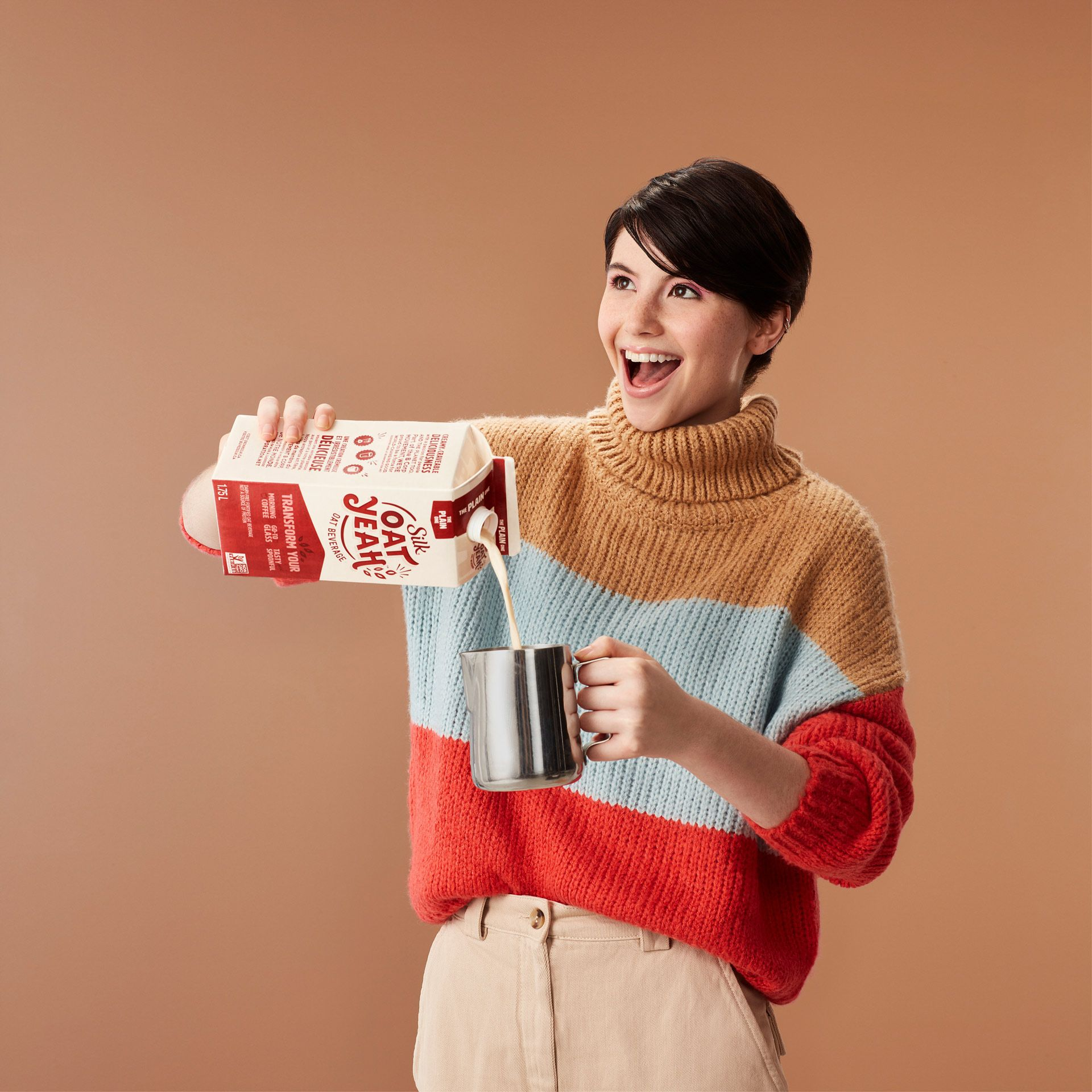 woman short black hair smiling pouring oat milk into metal barista cup wearing colorful large sweater by Simon Duhamel for Silk Oat Yeah and Carl agency