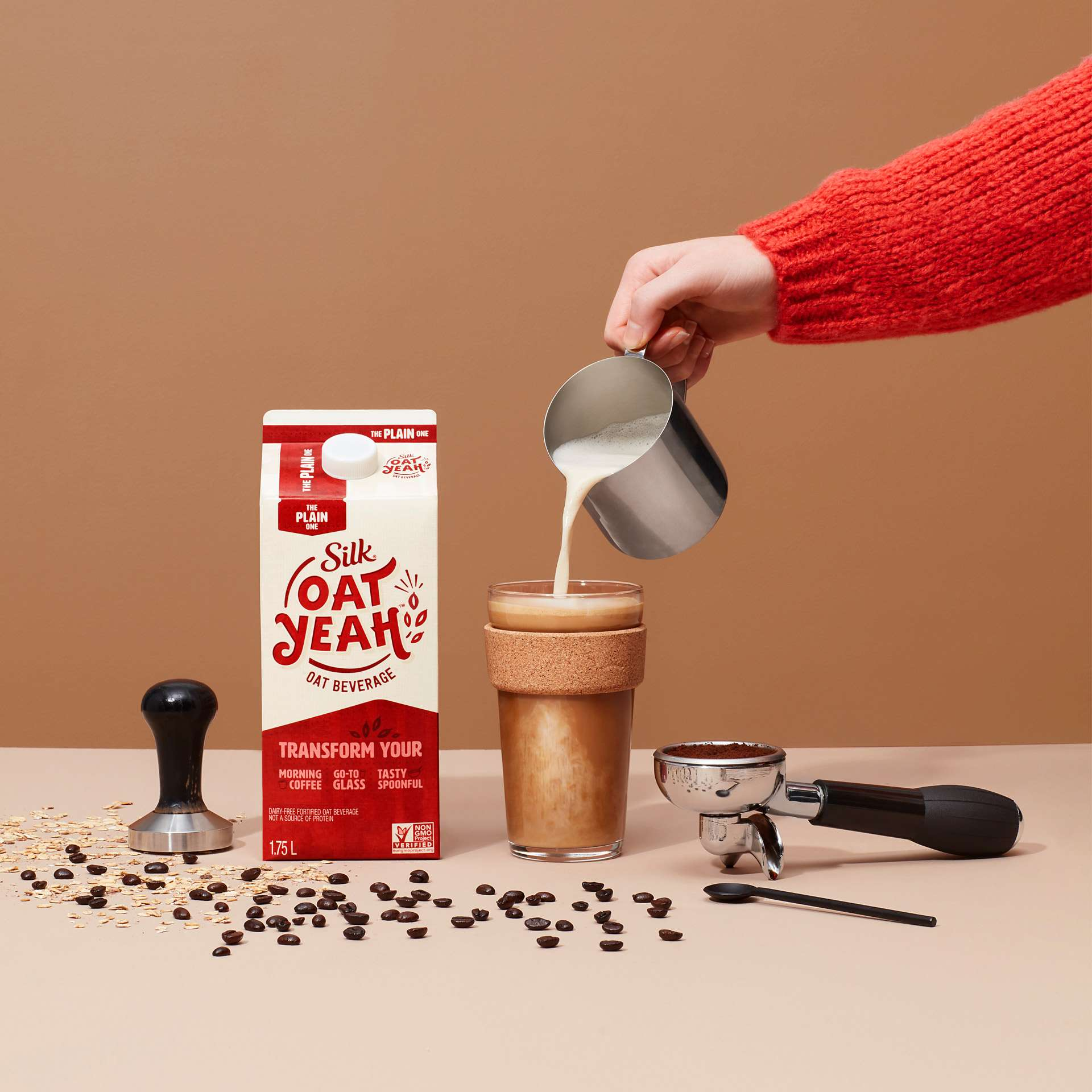 carton of plain oat milk beside tall glass hand pouring warm foaming milk into coffee in glass by Simon Duhamel for Oat Yeah Silk and Carl agency