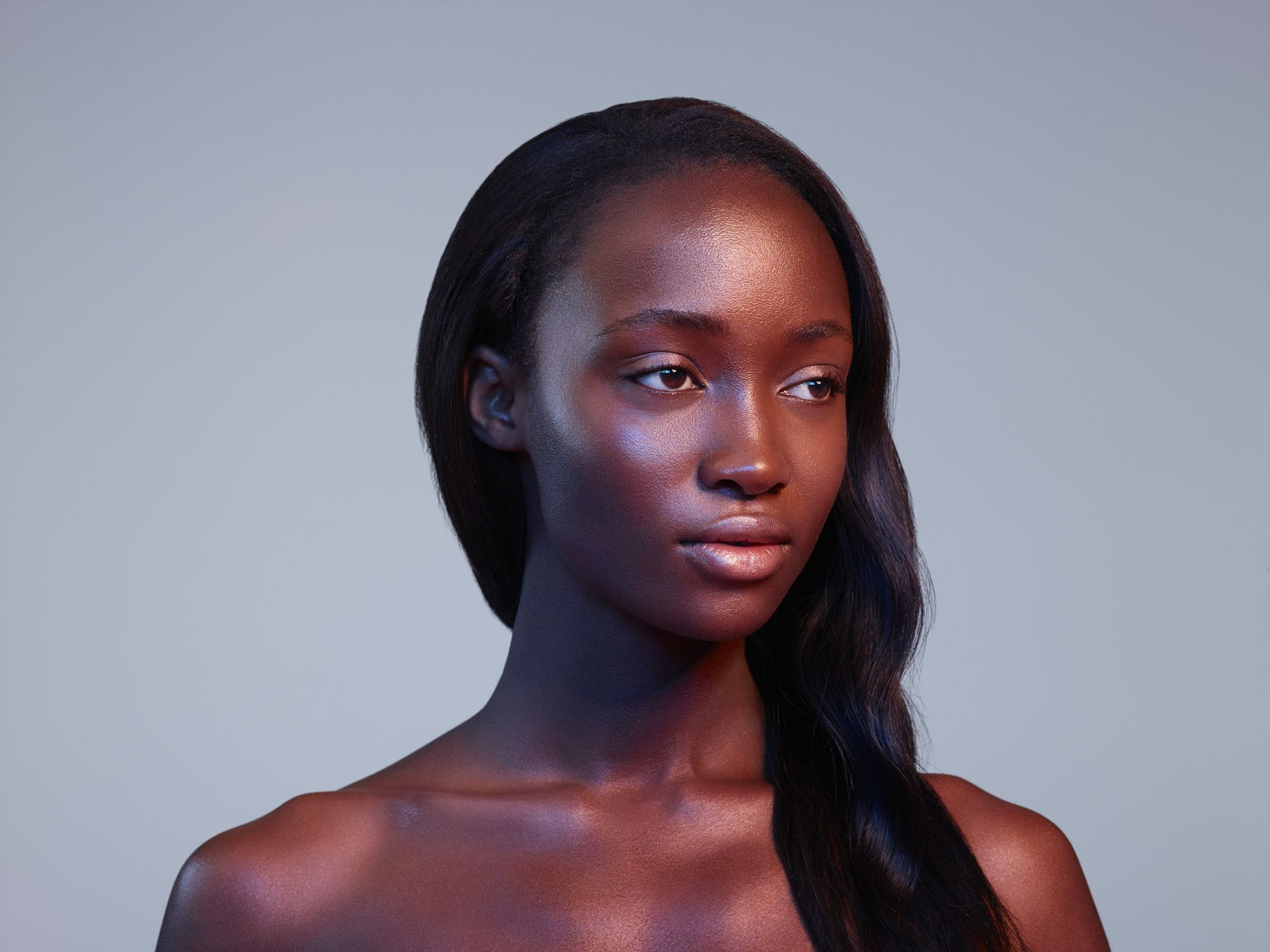 black woman well groomed hair looking away from camera in coloured lights on light pink background by Simon Duhamel for Skintone