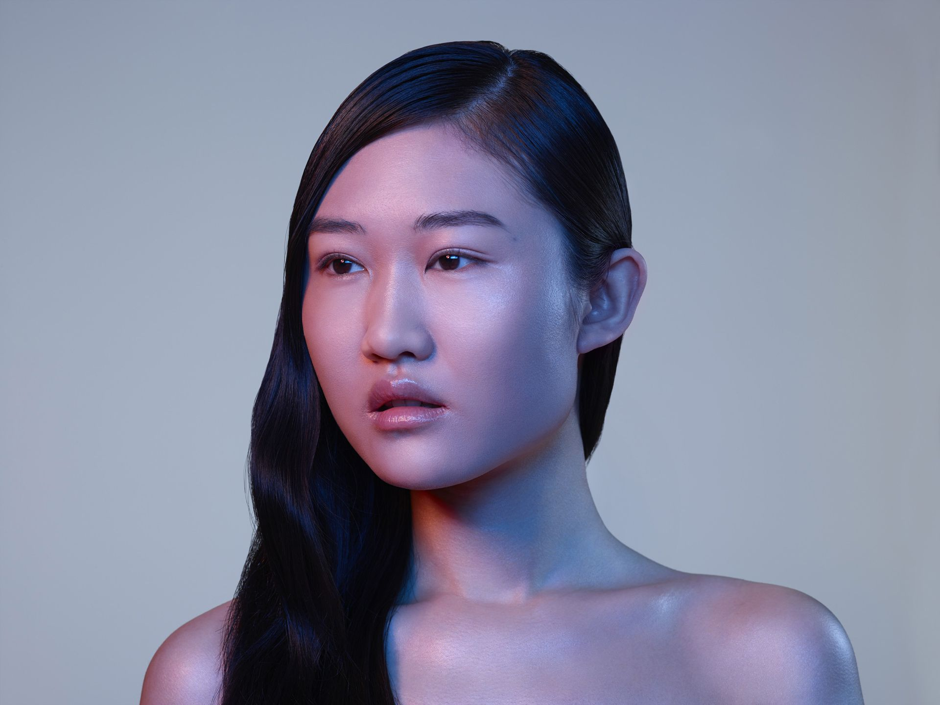 asian woman soft face well groomed black hair looking away from camera in cold coloured lights on light pink background by Simon Duhamel for Skintone