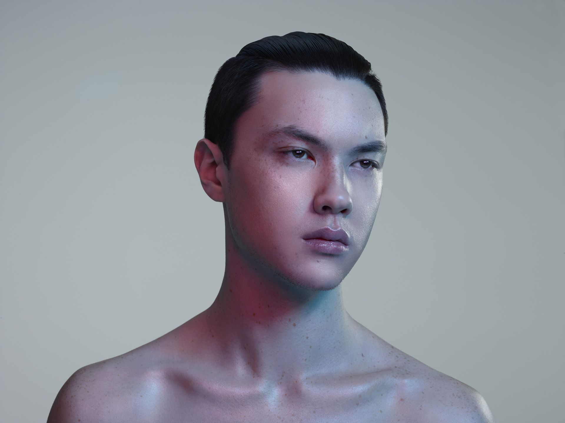 asian man with freckles slicked back black hair looking away from camera in cold coloured lights on light pink background by Simon Duhamel for Skintone