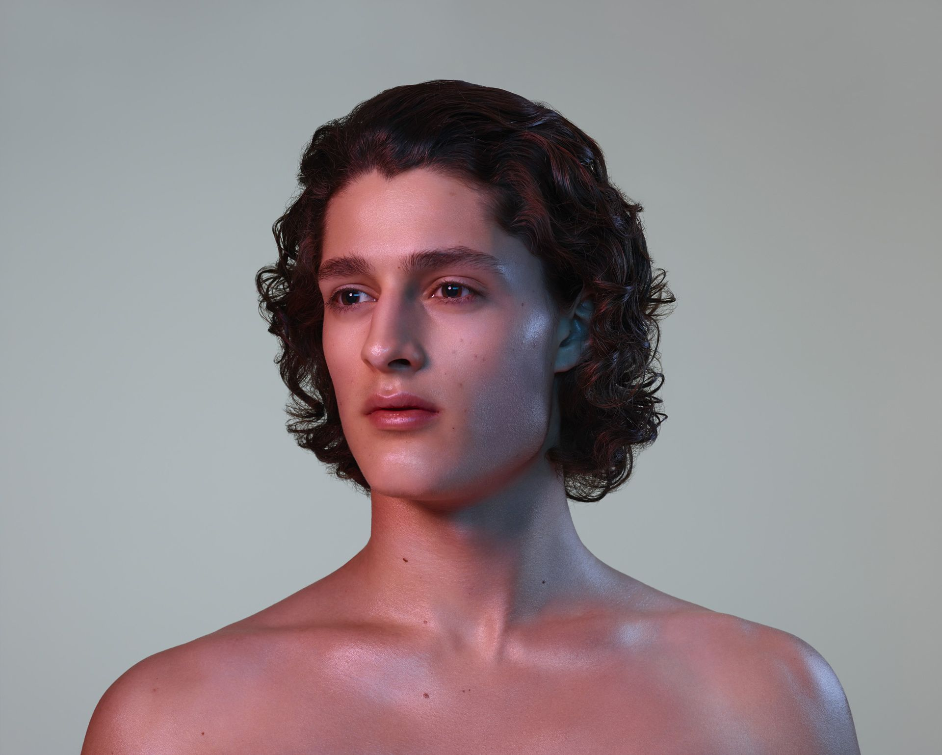 caucasian man well groomed brown curly hair looking away from camera in warm coloured lights on light pink background by Simon Duhamel for Skintone