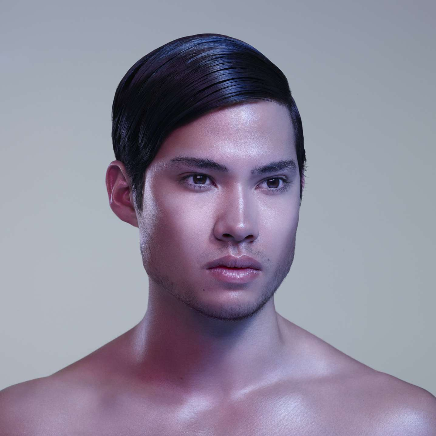asian man slicked hair light beard light pink background soft coloured lights by Simon Duhamel for Skintone