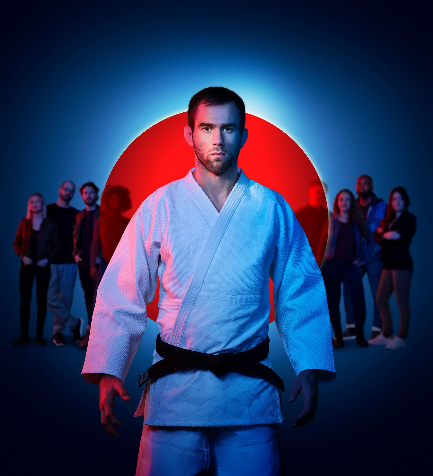 Martial arts olympic athlete posing in front of a crowd with blue lights and a red dot.