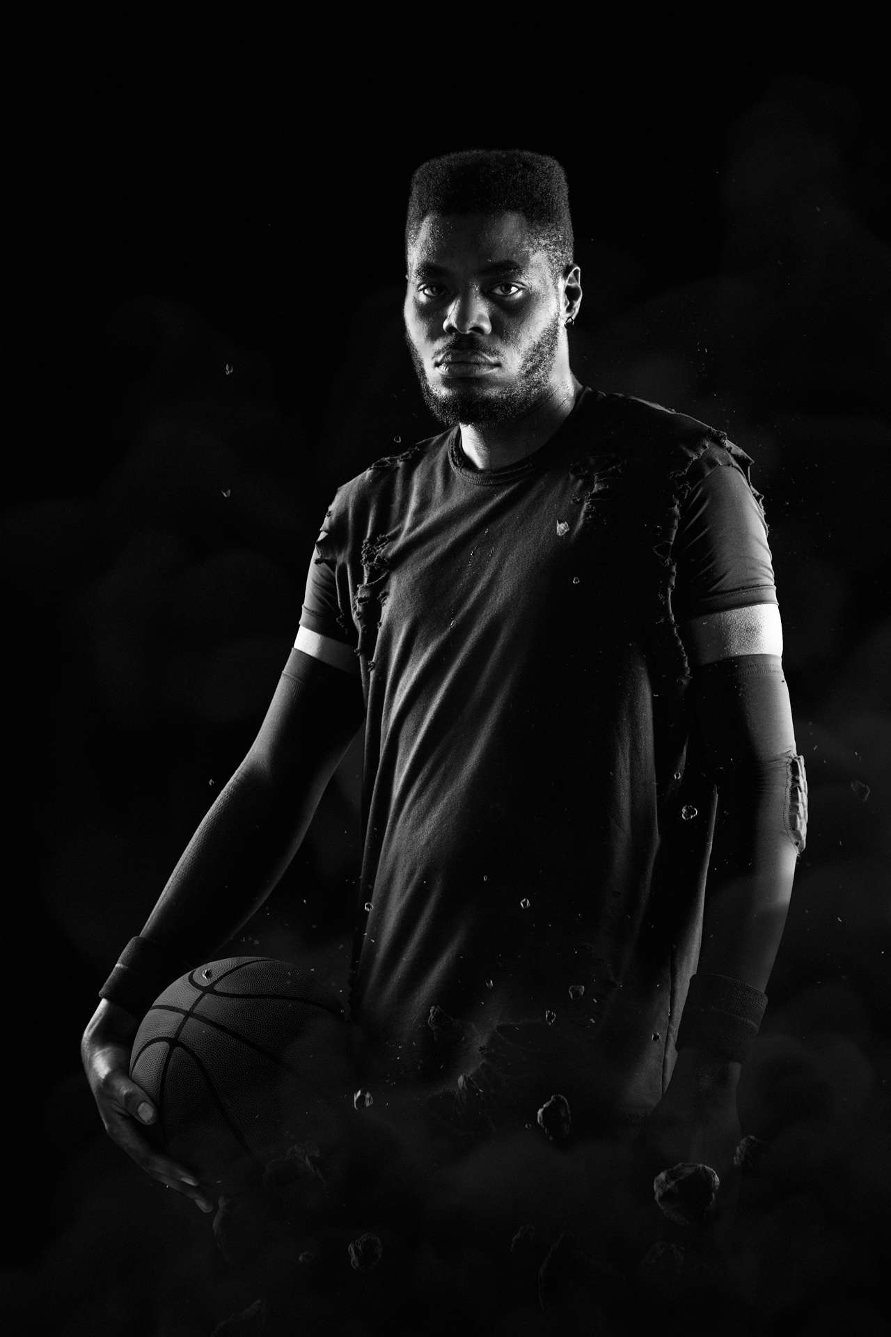 black man posing as basketball player looking at camera holding basket ball low lighting black and white by Simon Duhamel for W-Hoop