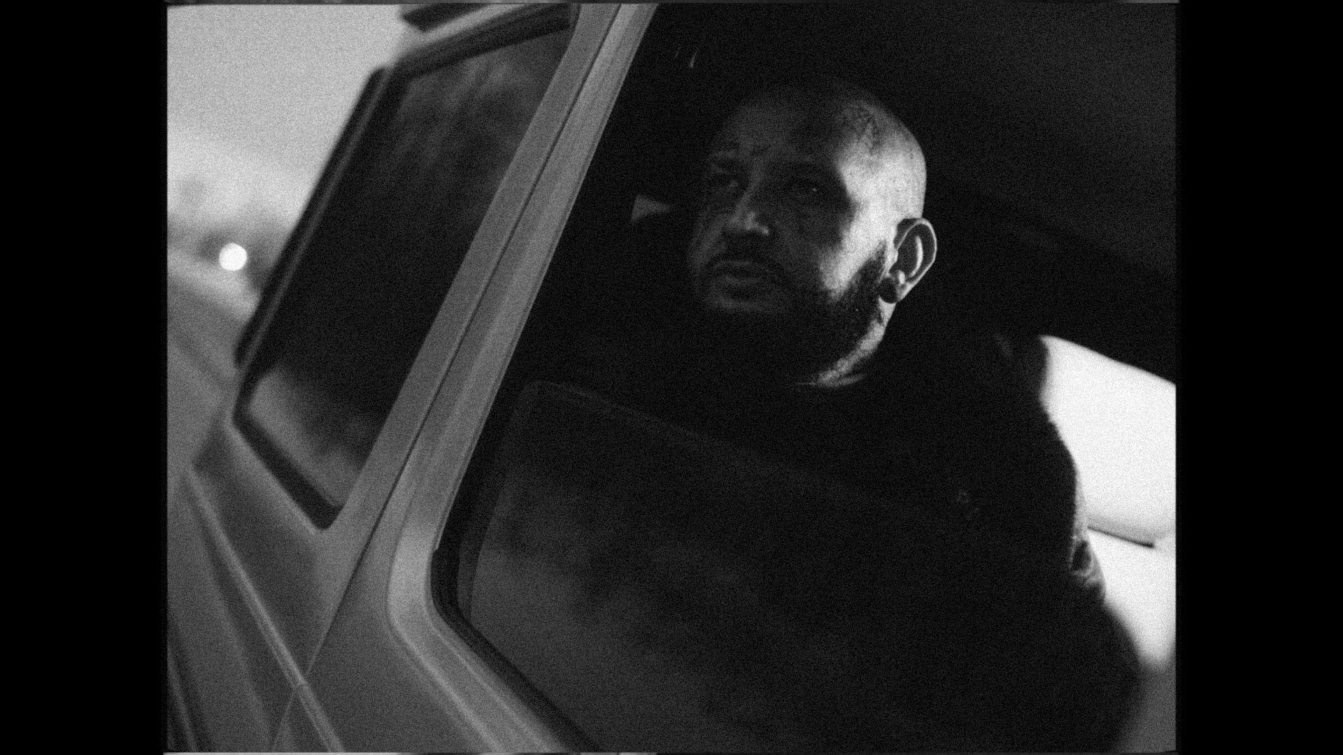 rapper Souldia in car looking out the window wearing sinter coat for his music video Rouge Neige filmed by Les Gamins featuring Sinik, Seth Gueko and Rick Pagano