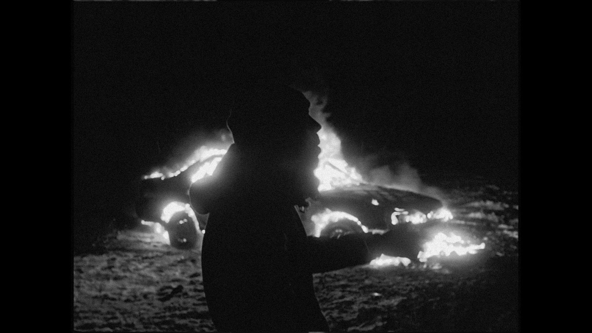 rapper Souldia singing in front of a car on fire in a field in winter for his music video Rouge Neige filmed by Les Gamins featuring Sinik, Seth Gueko and Rick Pagano