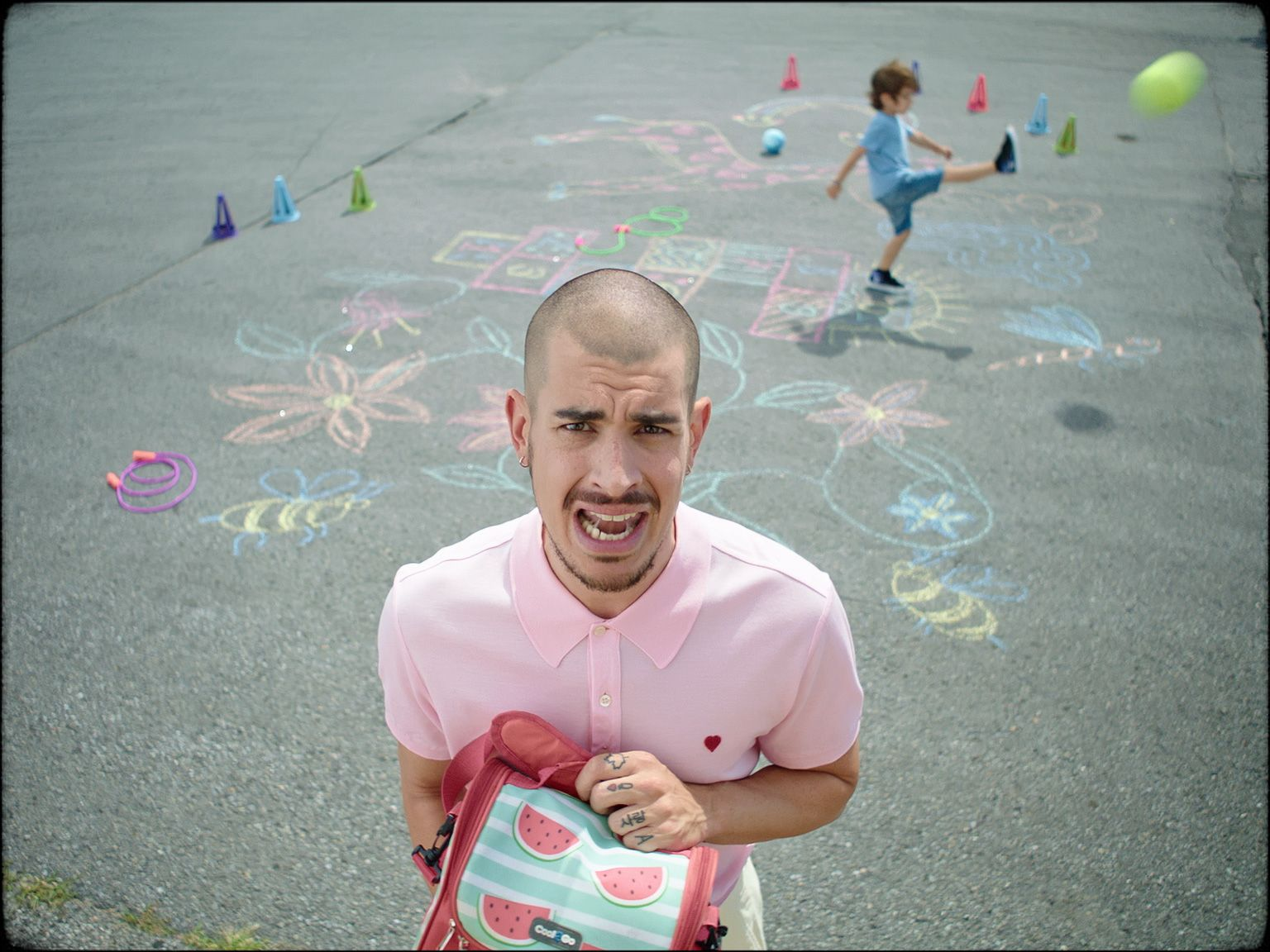 rapper Koriass wearing pink shirt holding strawberry themed backpack on school grounds in music video 5 à 7 filmed by Vincent Ruel-Cote from Les Gamins with 7ieme Ciel Records