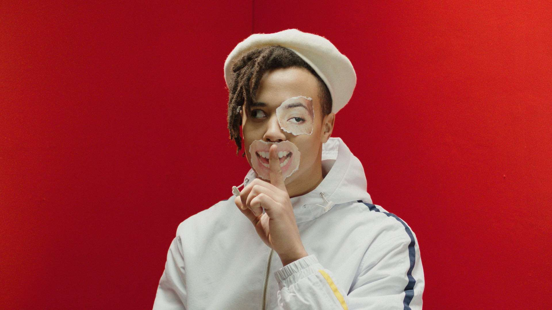 rapper Zach Zoya on red background with pieces of paper on his face for music video Who Dat filmed by Les Gamins