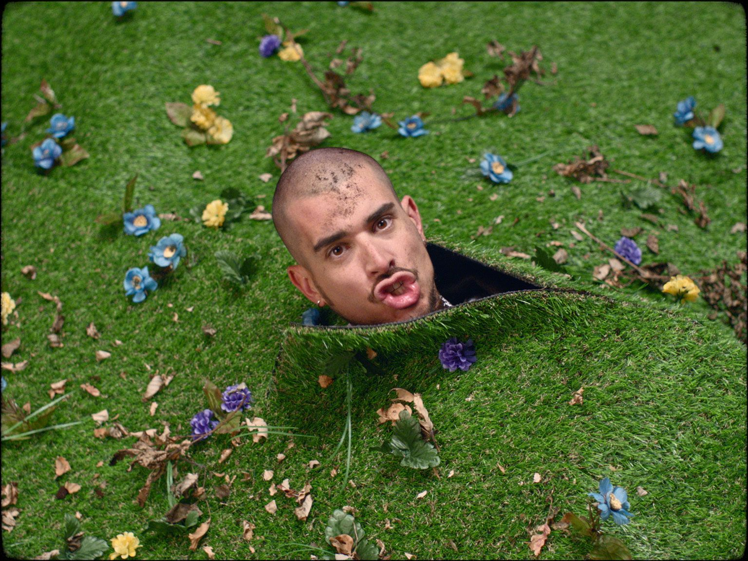 rapper Koriass head poking out of fake grass in music video 5 à 7 filmed by Vincent Ruel-Cote from Les Gamins with 7ieme Ciel Records