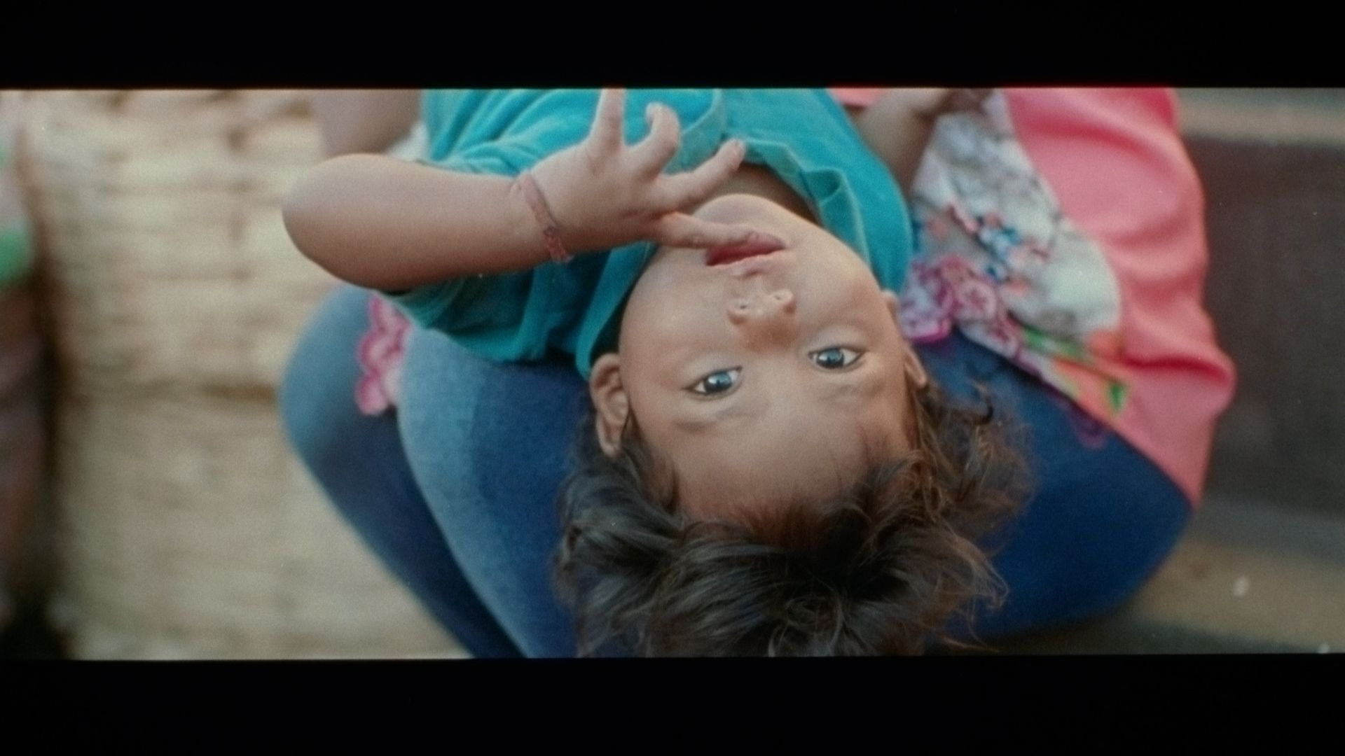 young kid laying in a woman's arms looking at camera upside down with fingers in their mouth singer Karim Ouellet music video of La Mer A Boire filmed by Les Gamins