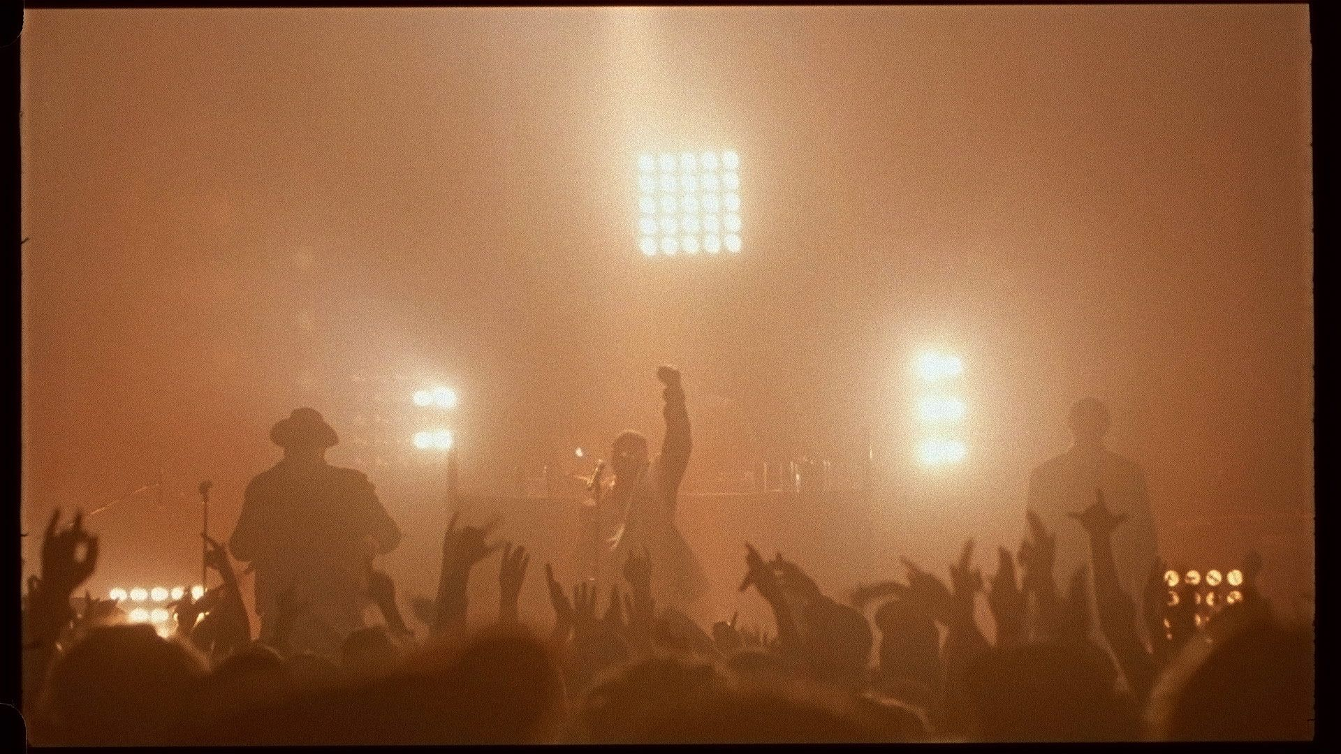 singer Brown on stage with his fist raised up in the air in front of crowd bathed in soft orange light for L'Osstidfilm documentary filmed by Vincent Ruel-Cote from Les Gamins about L'Osstidtour