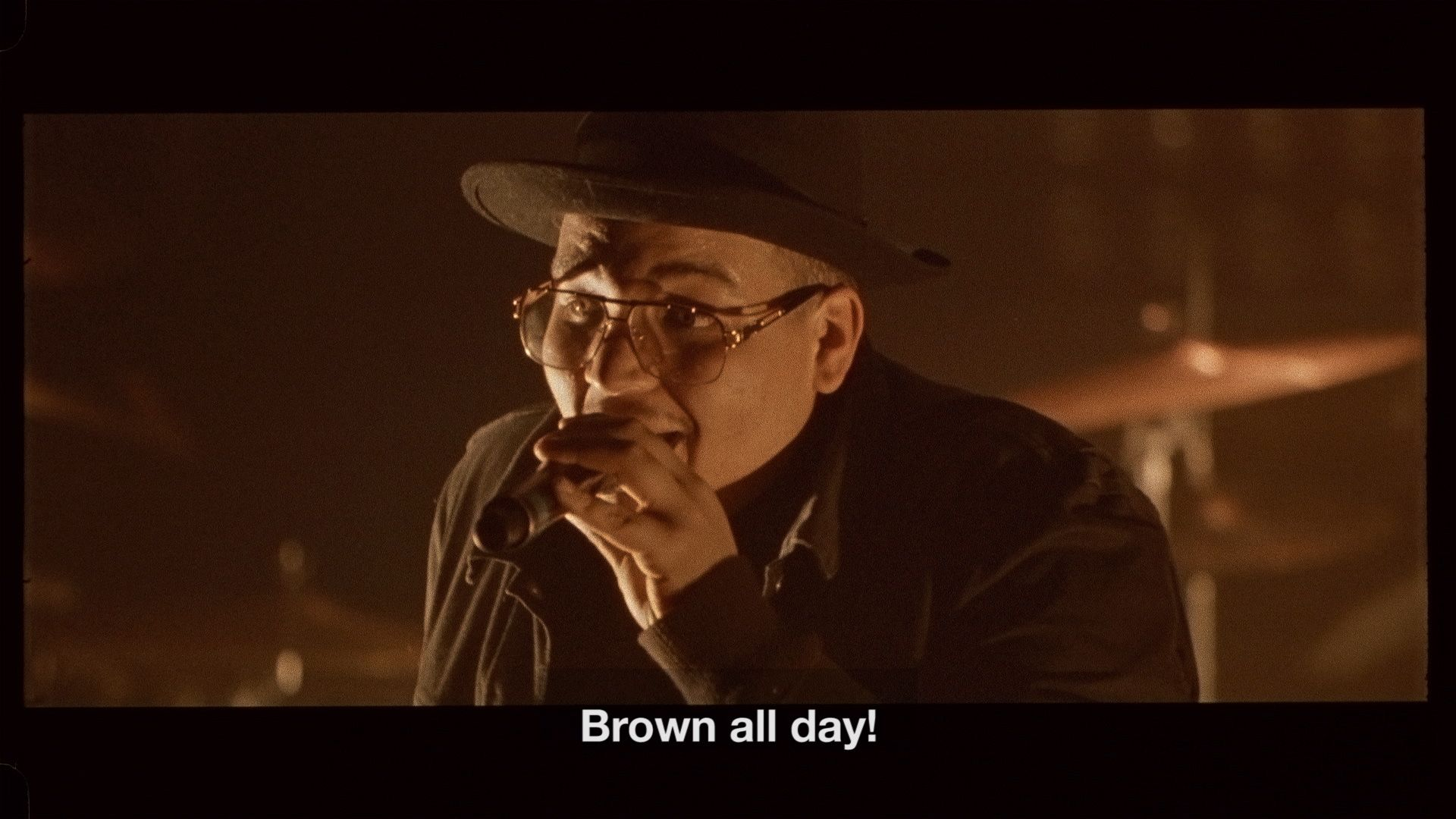 """singer Brown on stage singing """"Brown all day"""" bathed in soft orange light for L'Osstidfilm documentary filmed by Vincent Ruel-Cote from Les Gamins about L'Osstidtour"""