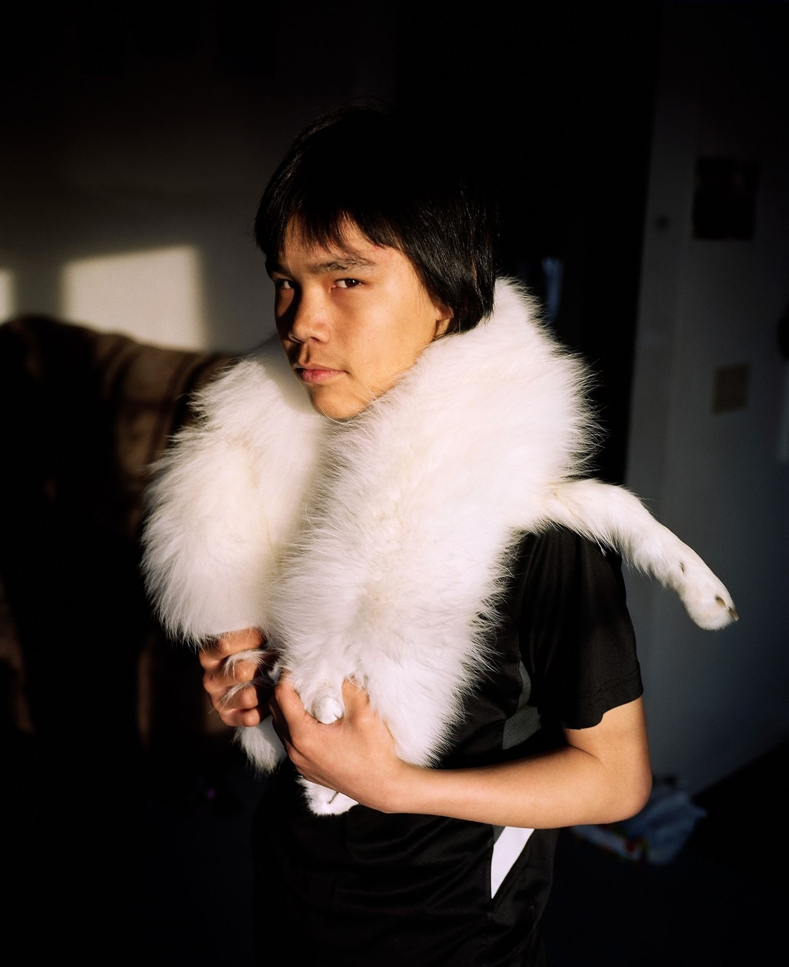 young boy wearing pelt of white arctic fox fur around his neck looking at camera photographed by Guillaume Simoneau in Pond Inlet for Telegraph magazine