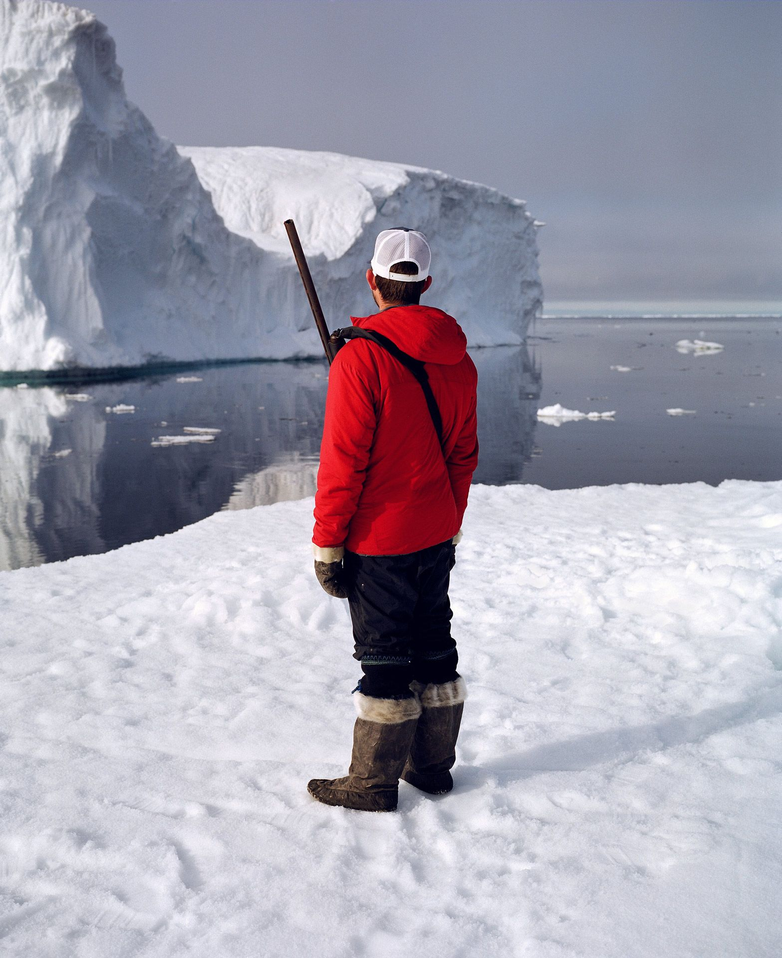 man standing on ice looking out to the horizon wearing red winter coat and a shotgun photographed by Guillaume Simoneau in Pond Inlet for Telegraph magazine