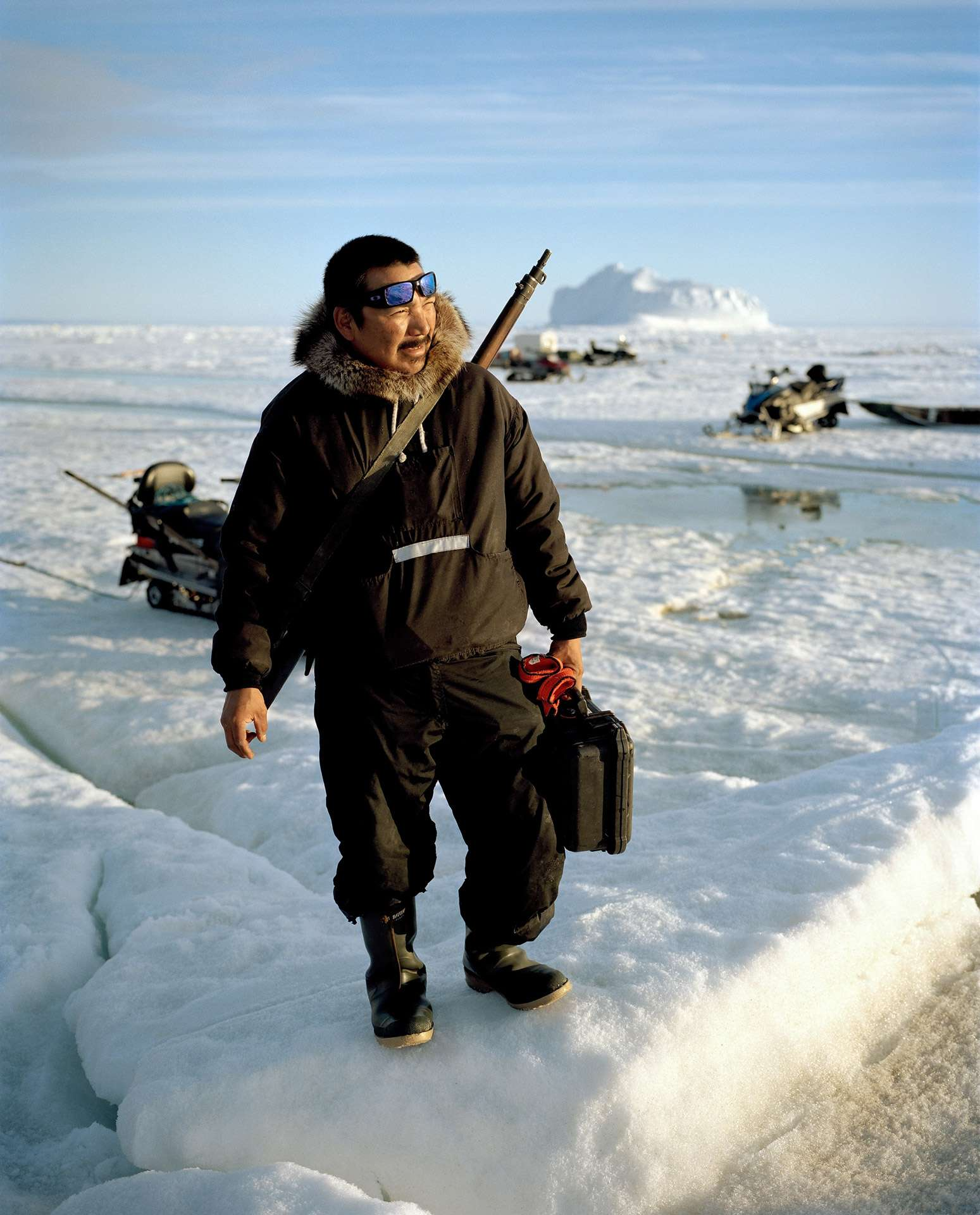 man on ice block wearing black winter coat and shotgun around his torso holding black case photographed by Guillaume Simoneau in Pond Inlet for Telegraph magazine
