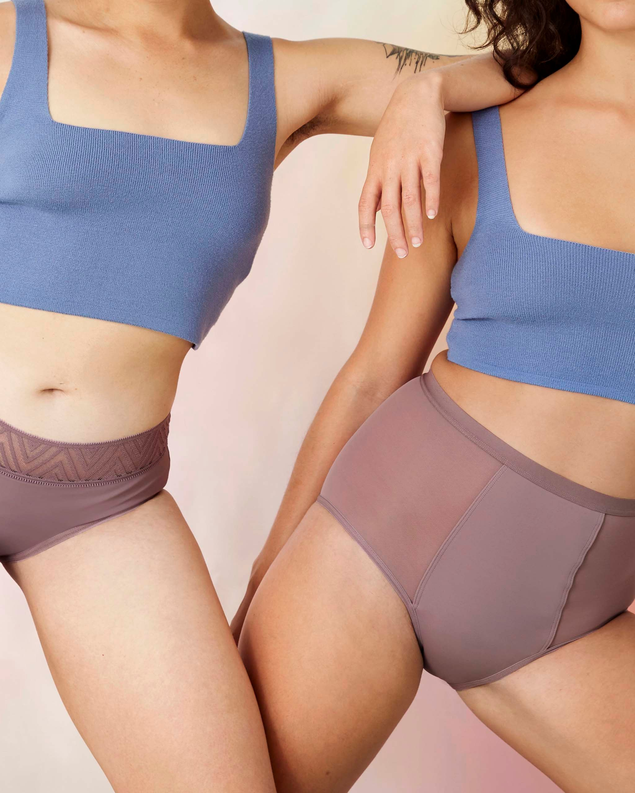 Close up of bodies, two girls are wearing pink Thinx period underwear with blue tank tops.